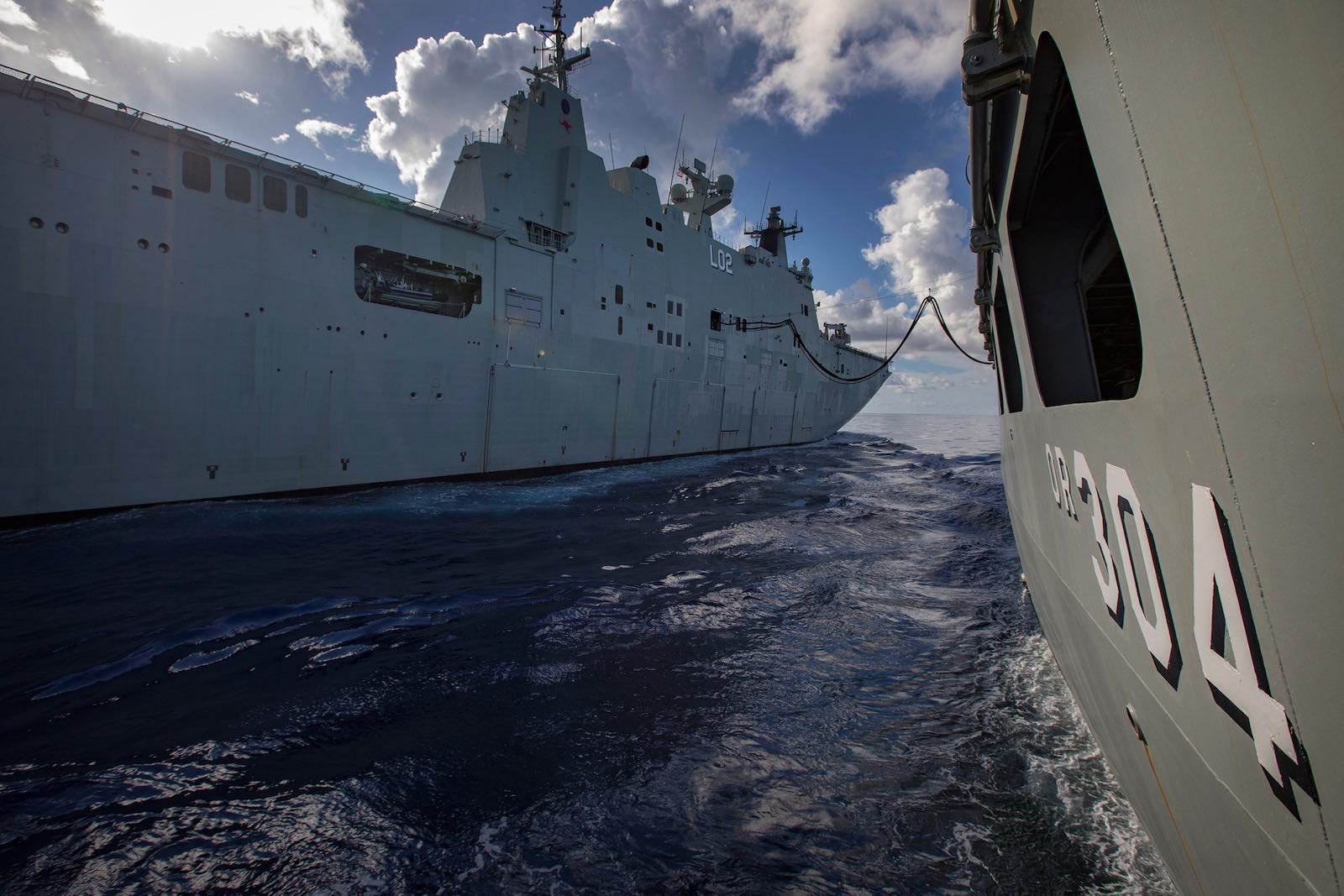 HMAS Canberra connects alongside HMAS Success during replenishment at sea (Photo: Defence Department)