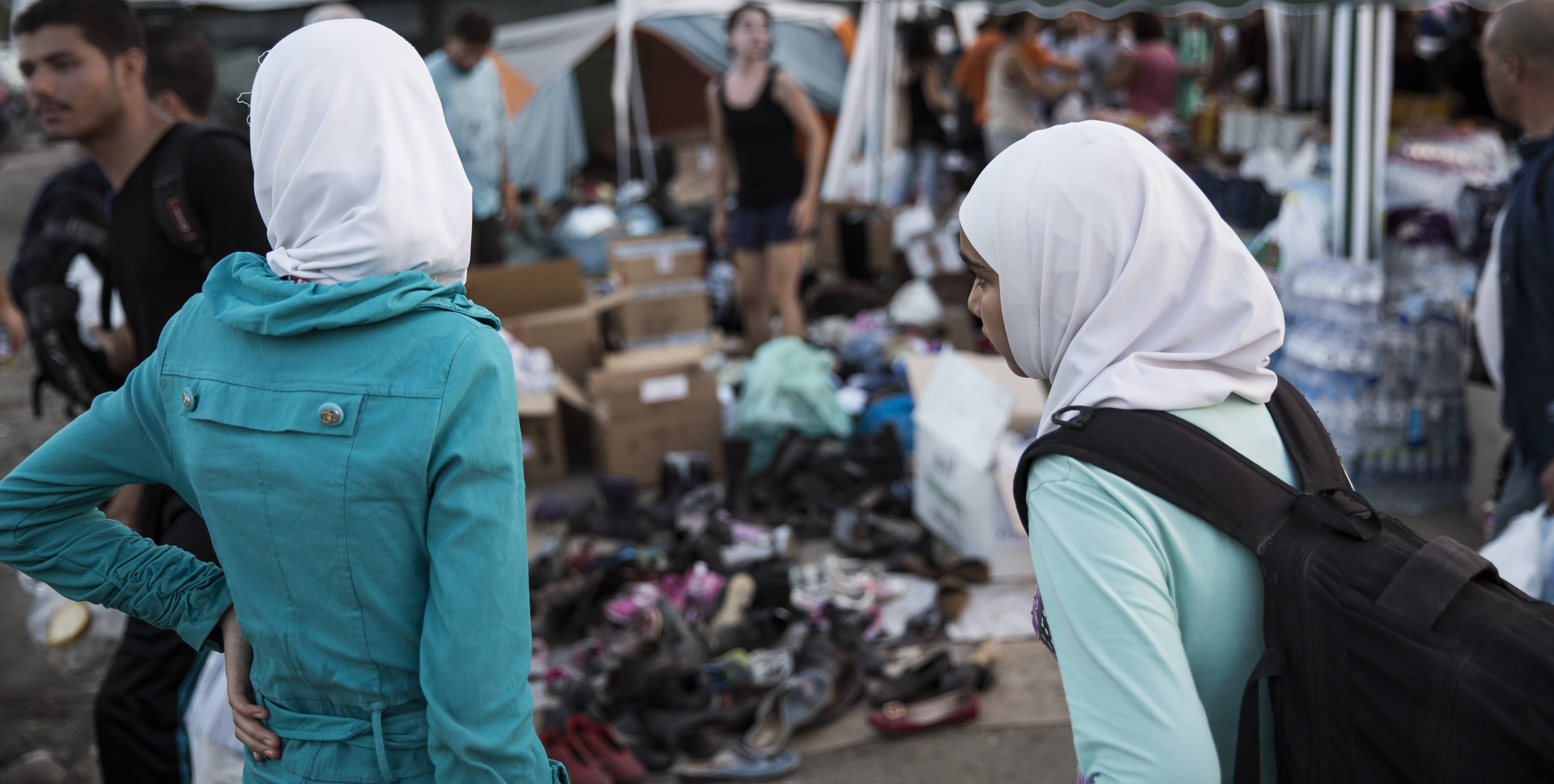 Sisters wait at a before crossing in Greece in 2015 (Photo: IOM/Flickr)