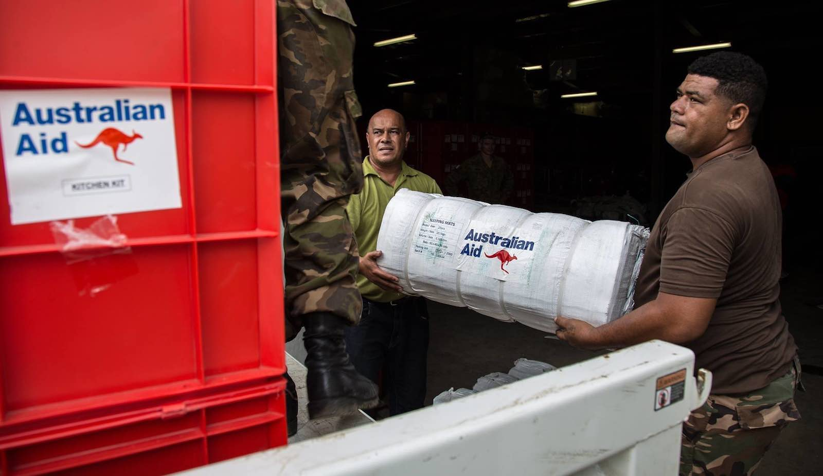 A volunteer helps a Tonga Defense Service soldier unload Australian aid supplies after Cyclone Gita, May 2018 (Photo: AHC Nakualofa/Flickr)