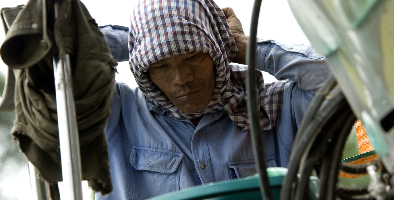 A migrant worker puts on a scarf before harvesting rice (Photo: ILO/ Flickr)