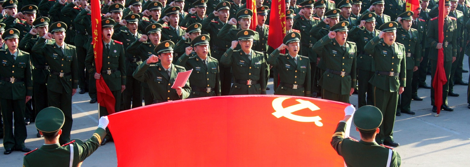 Soldiers saluting the Chinese Communist Party flag in Beijing (Photo:Getty Images)