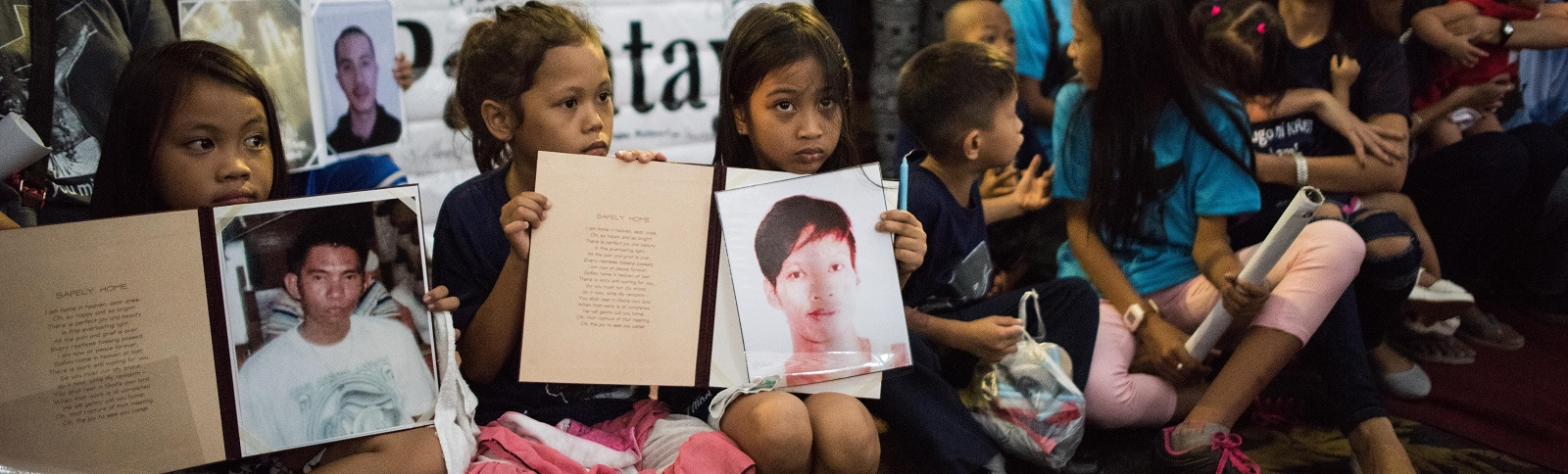 Children hold pictures of loved ones killed during a mass held for victims of the drug war on 2 February in Manila. (Photo by Dondi Tawatao/Getty Images)