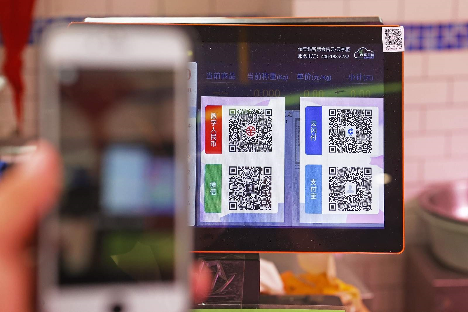 A customer chooses from QR payment codes for digital payment services e-CNY, UnionPay, Alipay and Wechat at a vegetable market in Shanghai on 7 May 2021 (Yin Liqin/China News Service via Getty Images)