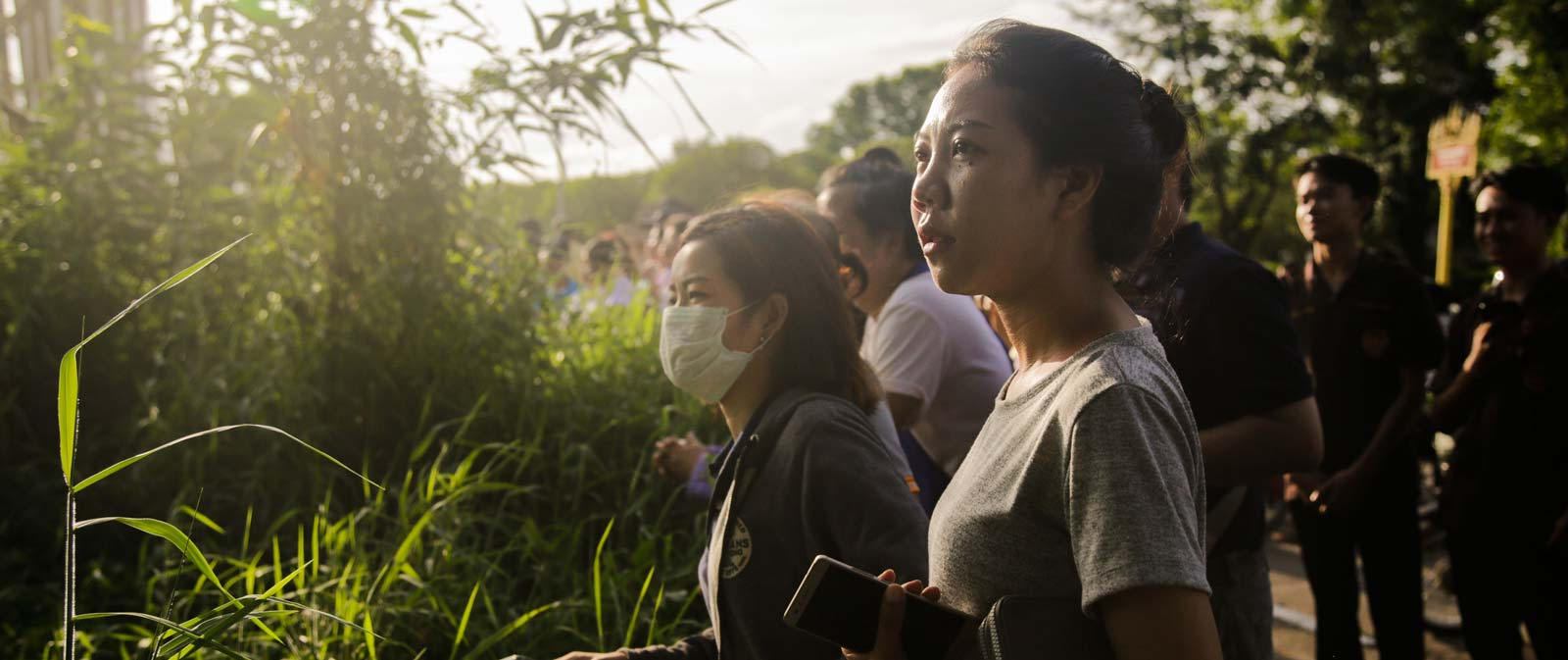 Onlookers watch as a helicopter flies towards Tham Luang Nang Non cave, Chian Rai, Thailand (Photo: Lauren DeCicca/Getty Images)