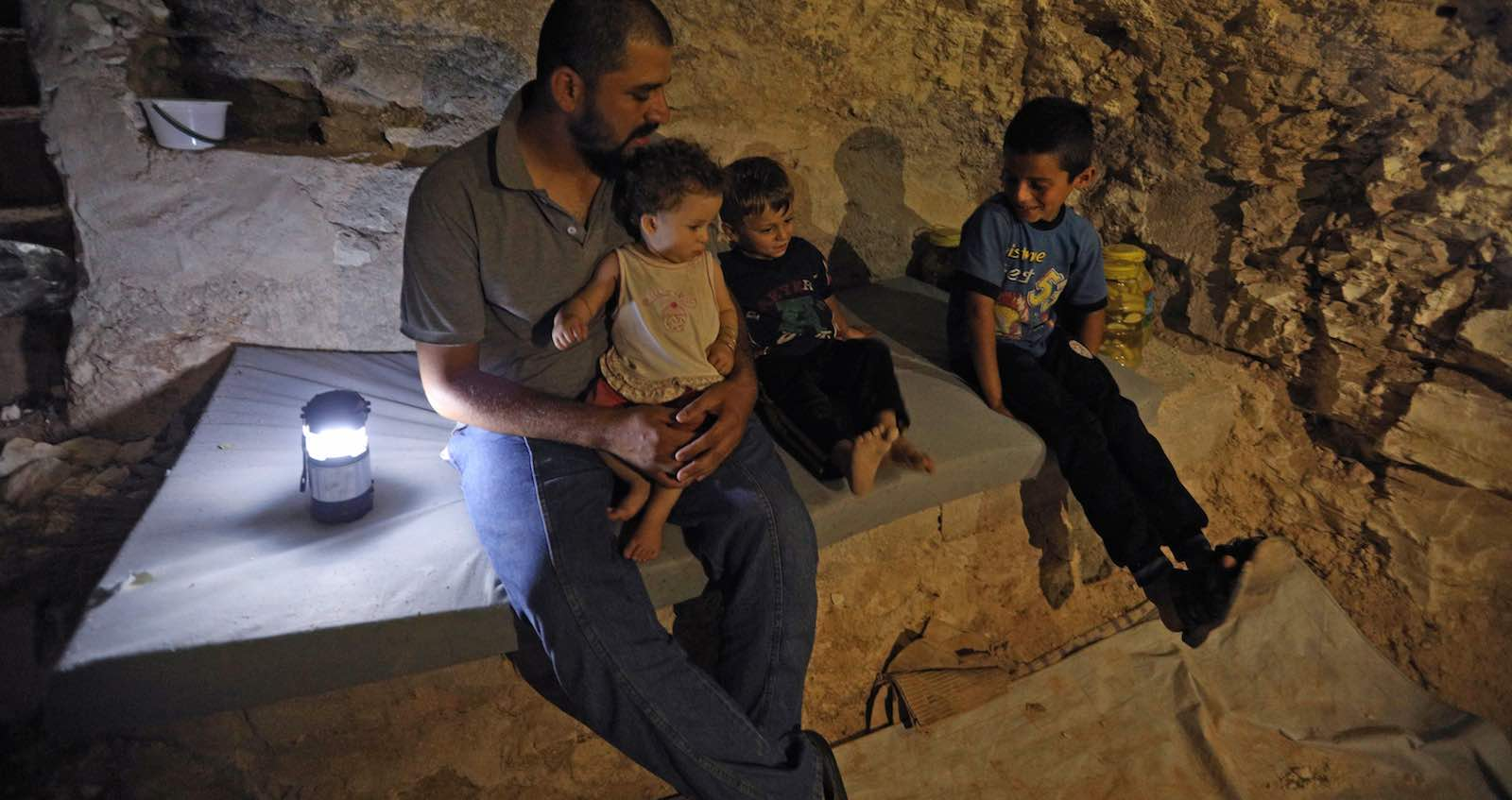 A family in an underground bunker, preparing for strikes in Idlib province, Syria (`Photo: Omar Haj Kadour via Getty)