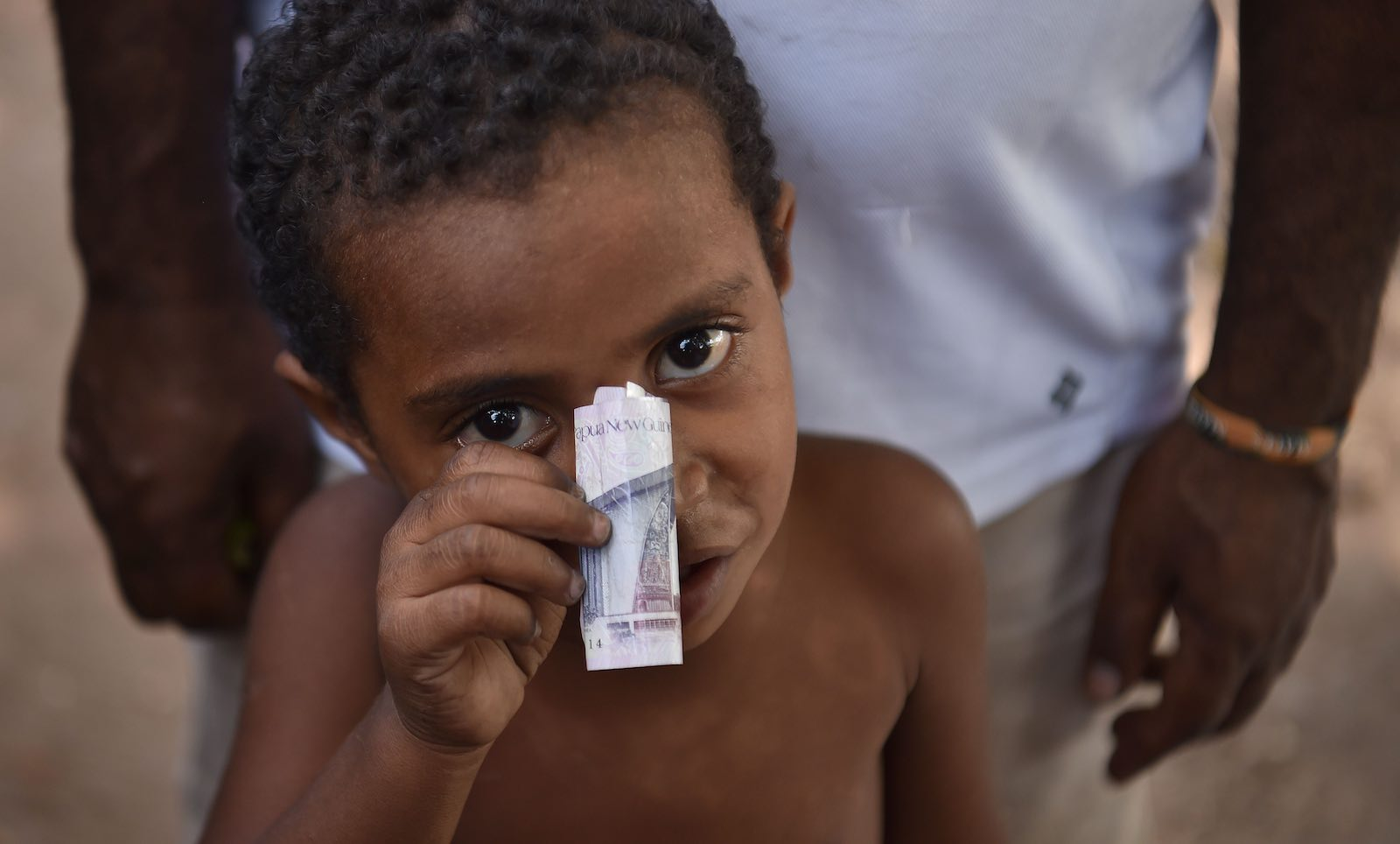 A boy and his kina, in Port Moresby (Photo: Peter Parks/AFP/Getty Images)