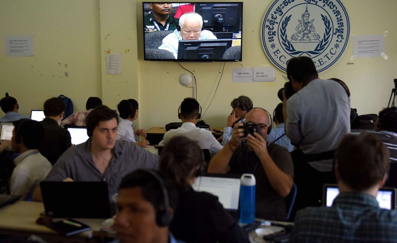 Journalists watch the verdict for former Khmer Rouge leader Khieu Samphan shown on a live video broadcast on 16 November (Photo: Tang Chhin Sothy via Getty)