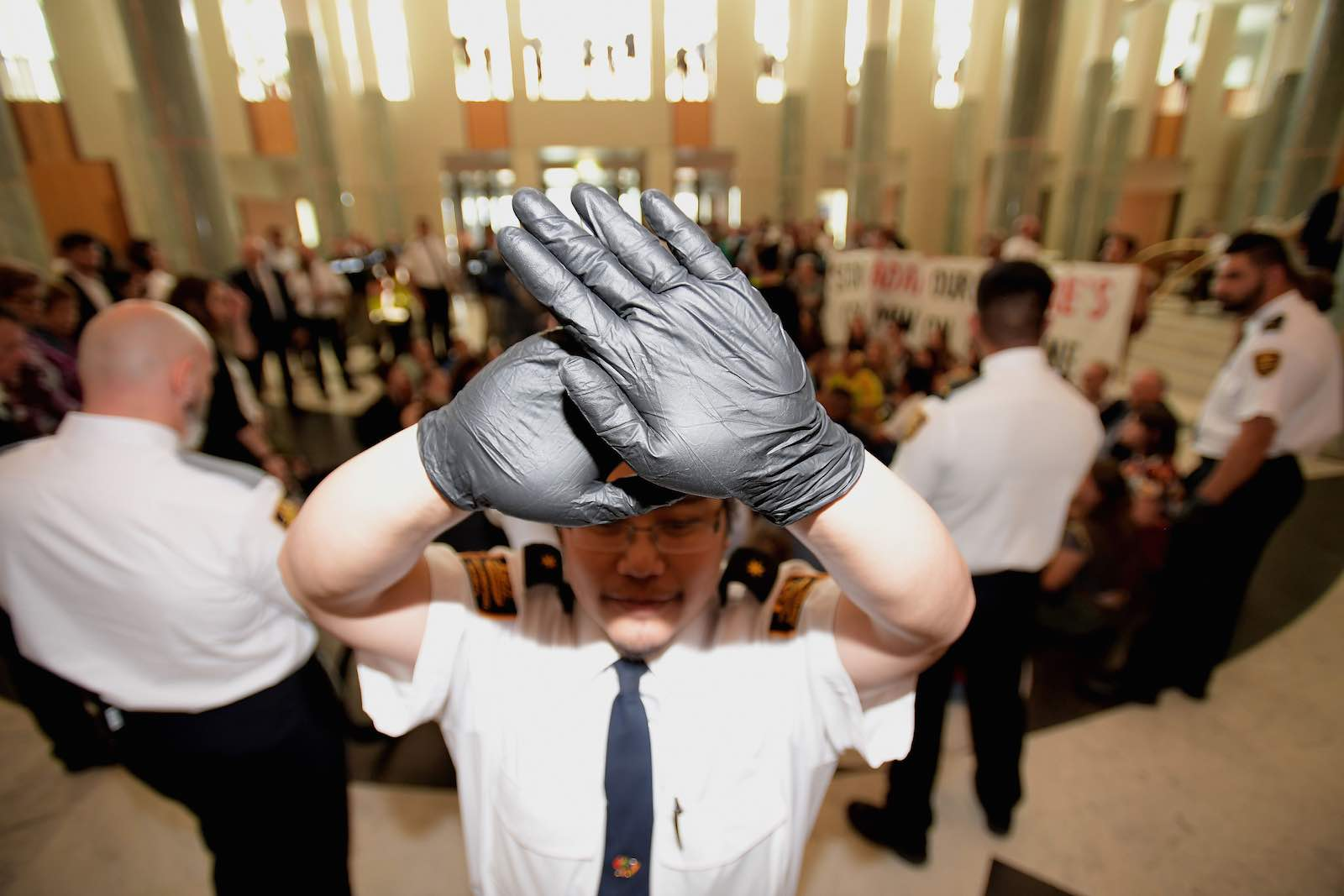 A security guard blocks photographers during a protest as parliament passes data-encryption legislation, Canberra, December 2018 (Photo: Tracey Nearmy/Getty Images)