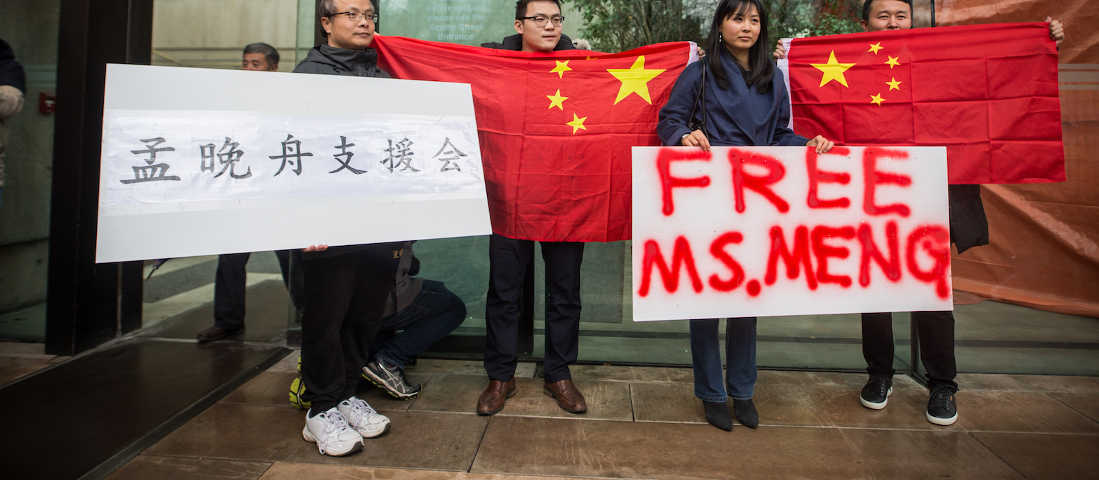 People hold signs and Chinese flags in support Meng Wanzhou outside the Supreme Court in Vancouver. (Photo: James MacDonald via Getty)