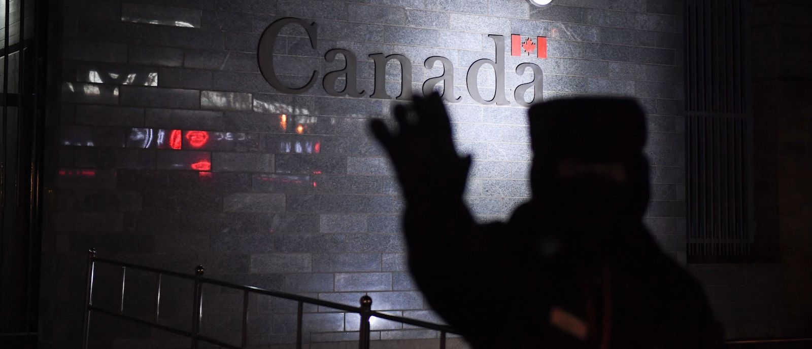 A guard tries to block photos being taken as he patrols outside the Canadian embassy in Beijing on 14 January (Photo: Greg Baker via Getty)