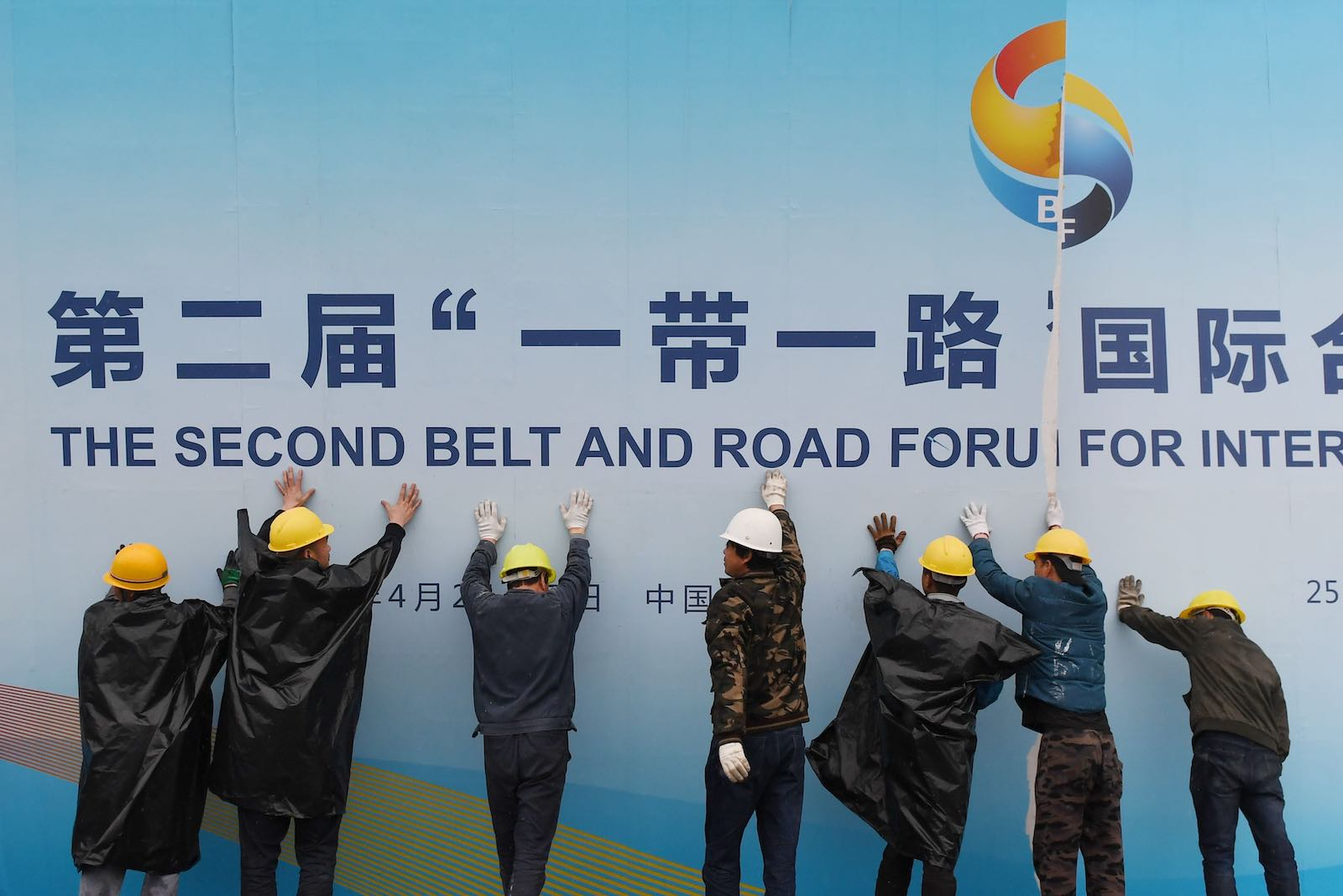 Workers take down a Belt and Road Forum panel outside the venue of the forum in Beijing in April (Photo: Greg Baker via Getty)