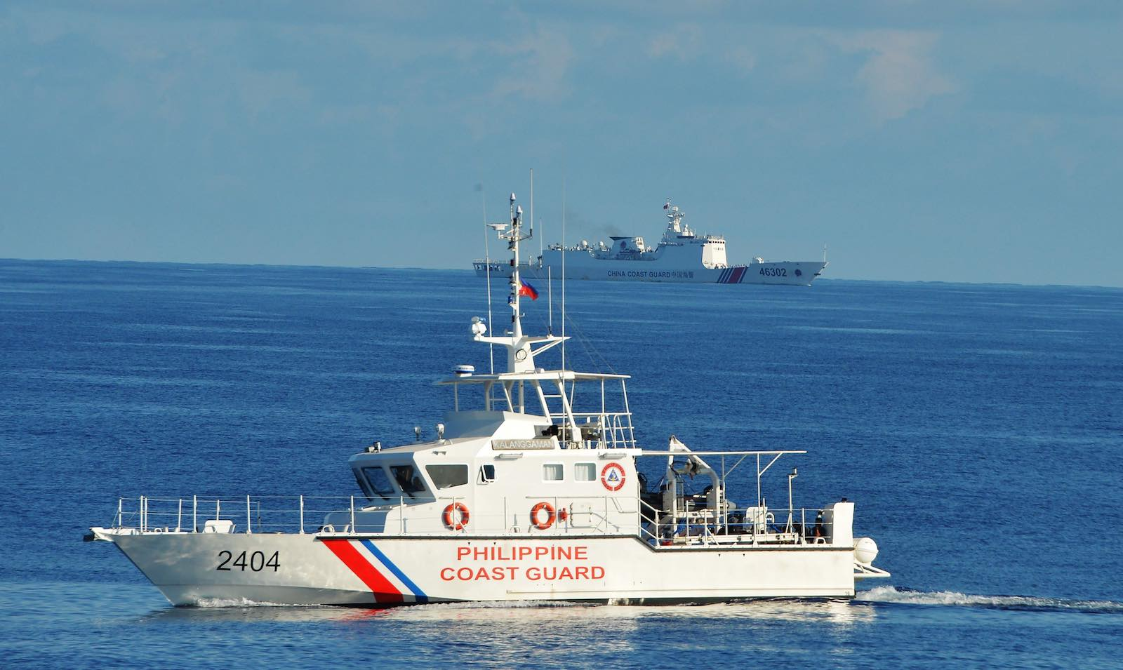 A Philippines coast guard ship sails past a Chinese coastguard ship near Scarborough shoal in the South China Sea in May 2019 (Ted Aljibe/AFP via Getty Images)