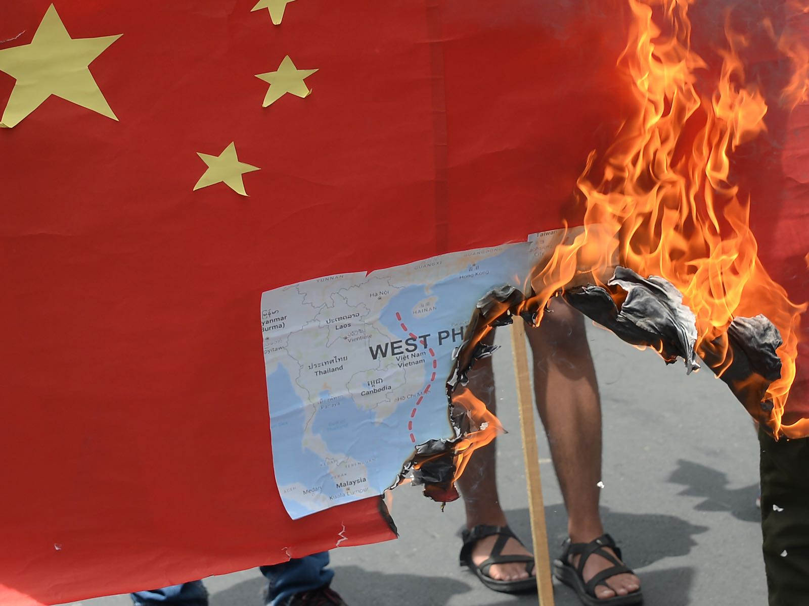 Protesters burn a mock Chinese flag with a map of the South China sea outside the Chinese consulate in Manila last year (Ted Aljibe/AFP via Getty Images)