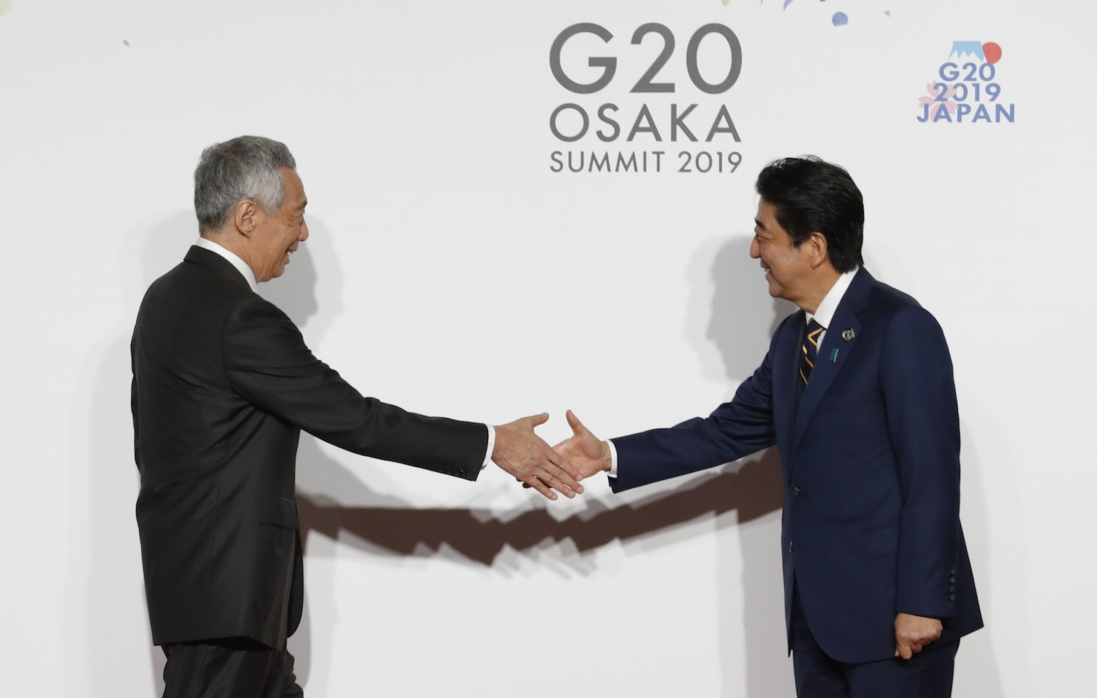 Singapore PM Lee Hsien Loong (L) is welcomed by Japanese PM Shinzo Abe at the G20 summit, June 2019 in Osaka, Japan. (Photo: Kim Kyung-Hoon via Getty)