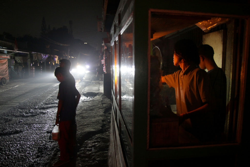 Food vendors serve customers by lantern light on 5 August, the second day of an electricity blackout in Wanasari Village, West Java