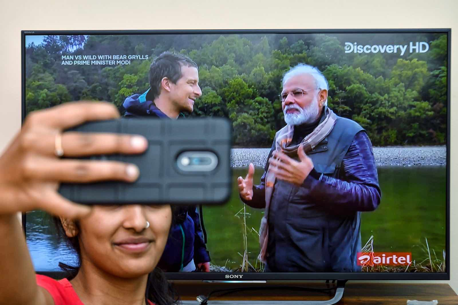 A fan in Bangalore snaps a selfie with the televised image of PM Modi (r) and Grylls (Photo: Manjunath Kiran via Getty)