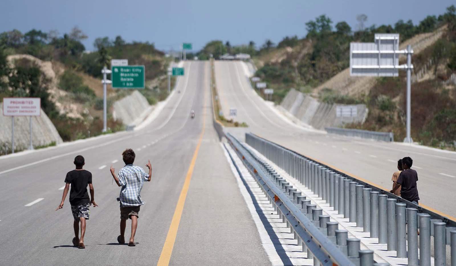 Young boys on an empty highway near Suai in Timor-Leste, built by the China Railway Group, 24 August 2019. (Photo: Dimas Ardian via Getty)