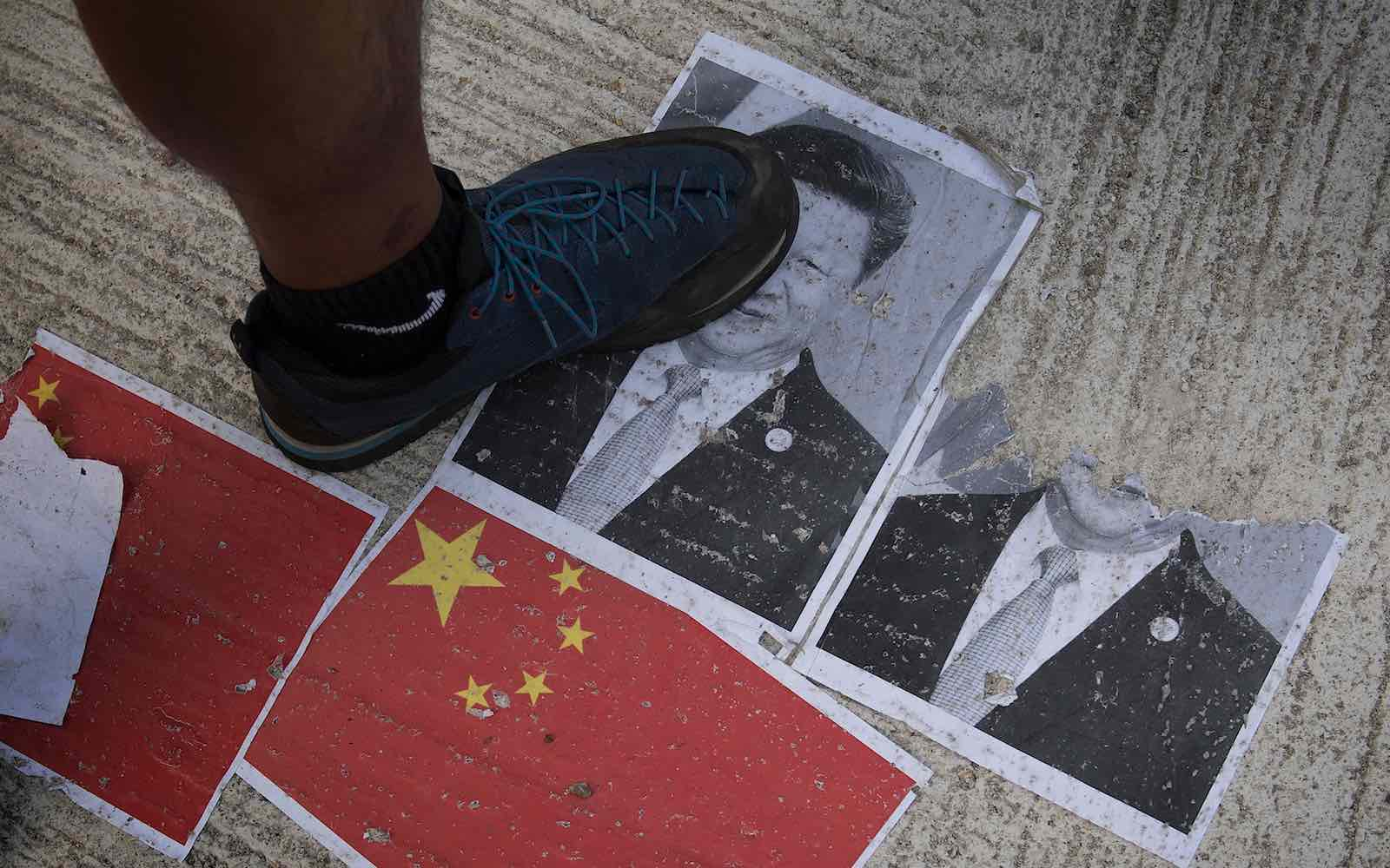 A protester treads on an image of Chinese President Xi Jinping in Hong Kong on 1 October 2019, the National Day marking the 70th anniversary of communist China's founding. (Photo: Mark Ralston/AFP via Getty)