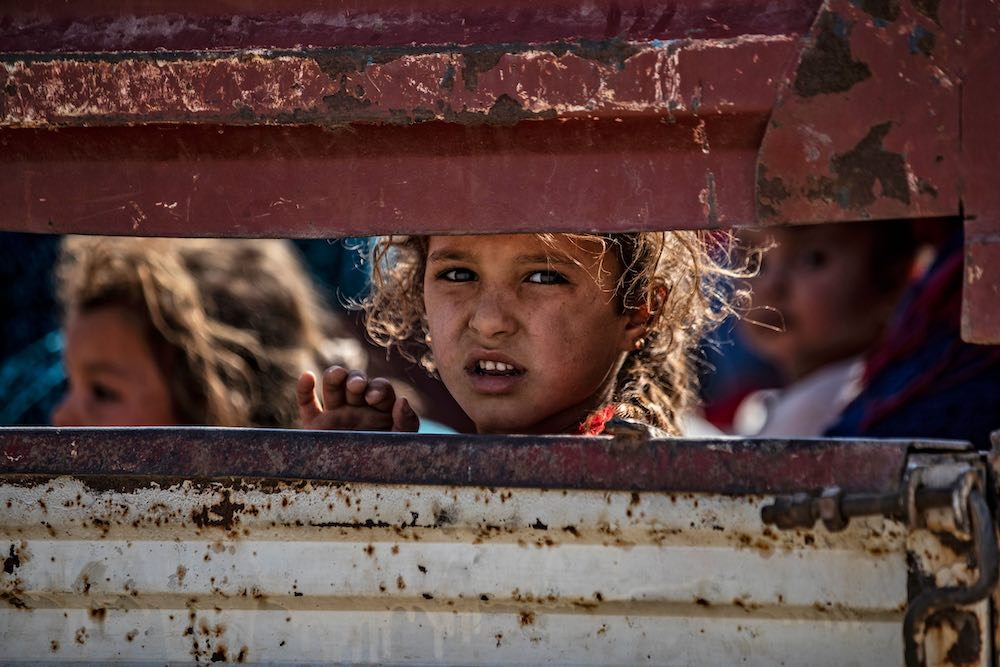 Syrian Arab and Kurdish civilians arrive at Tall Tamr town, in Syria's Hasakeh province, after fleeing Turkish bombardment along the border, 10 October 2019 (Photo: Delil Souleiman/AFP/Getty Images)