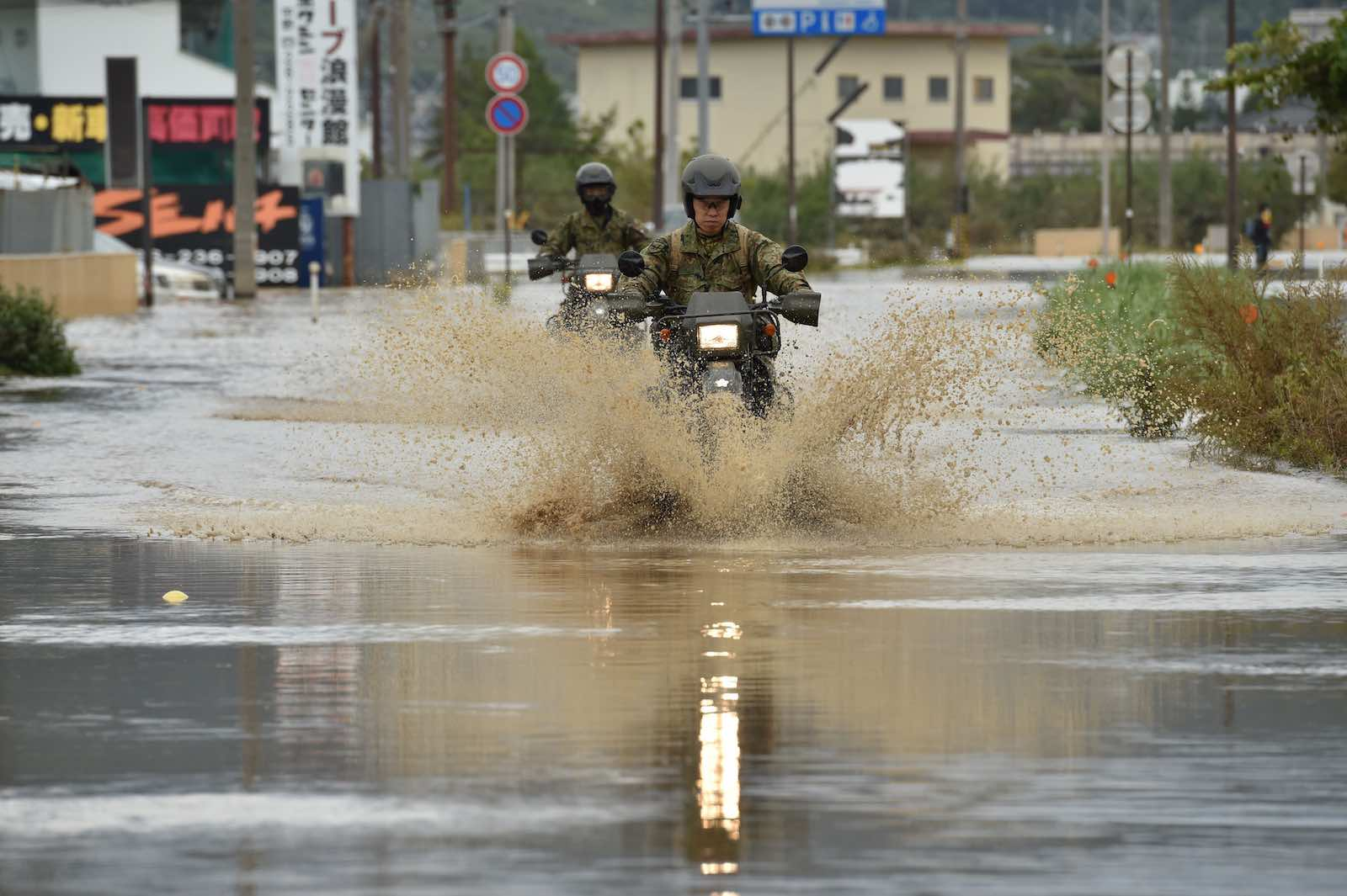 Military personnel drive their motorbikes down a flooded street in the aftermath of Typhoon Hagibis in Nagano on 14 October (Photo: Kazuhiro Nogi/AFP/Getty Images)