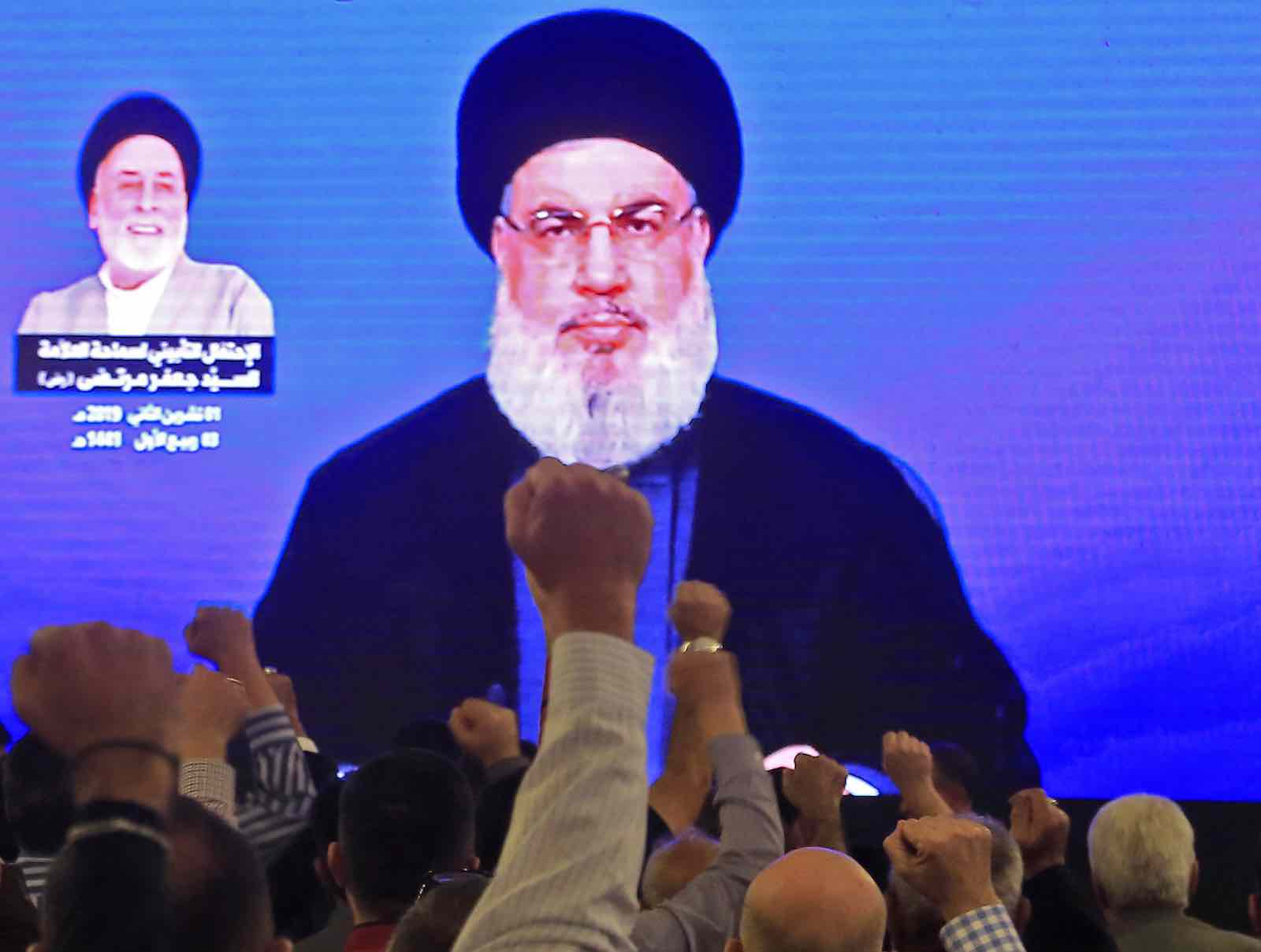 Supporters of Hassan Nasrallah, the head of Lebanon's militant Hezbollah movement, watch him speak through a giant screen at a mosque in Beirut's southern suburbs on 1 November (Photo: AFP via Getty Images)