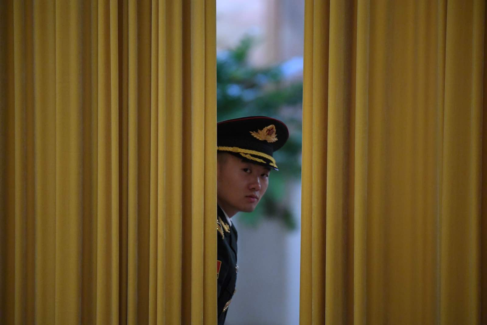 A Chinese honour guard peeks through a curtain before a welcome ceremony for Micronesia's President David Panuelo at the Great Hall of the People in Beijing in December (Photo: Noel Celis/AFP/Getty Images)