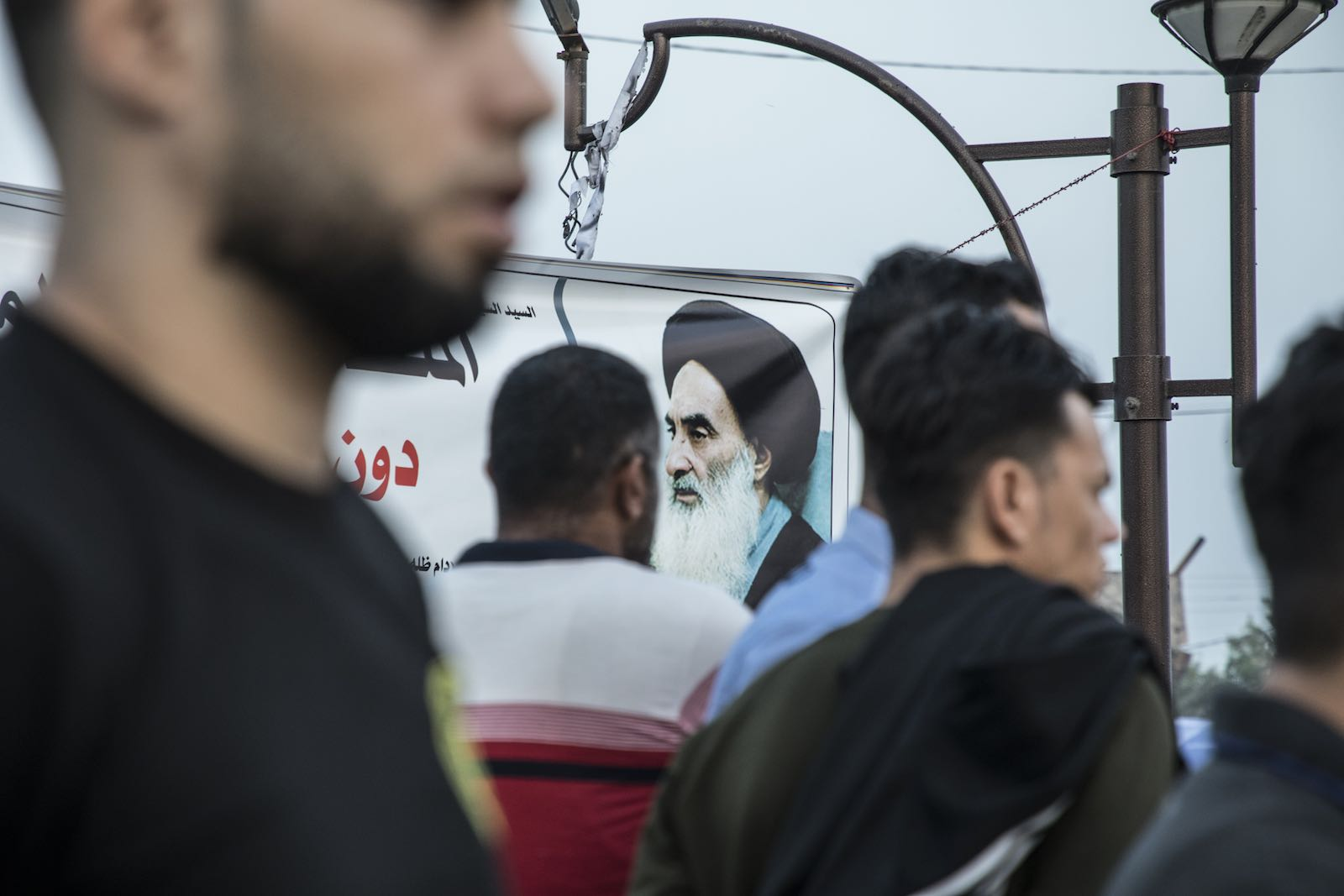Protestors in front of the governorate in Basra, Iraq, and a billboard of Shia leader Ali Al-Sistani, 16 November (Photo: Laurent Van der Stockt/Le Monde/Getty Images)