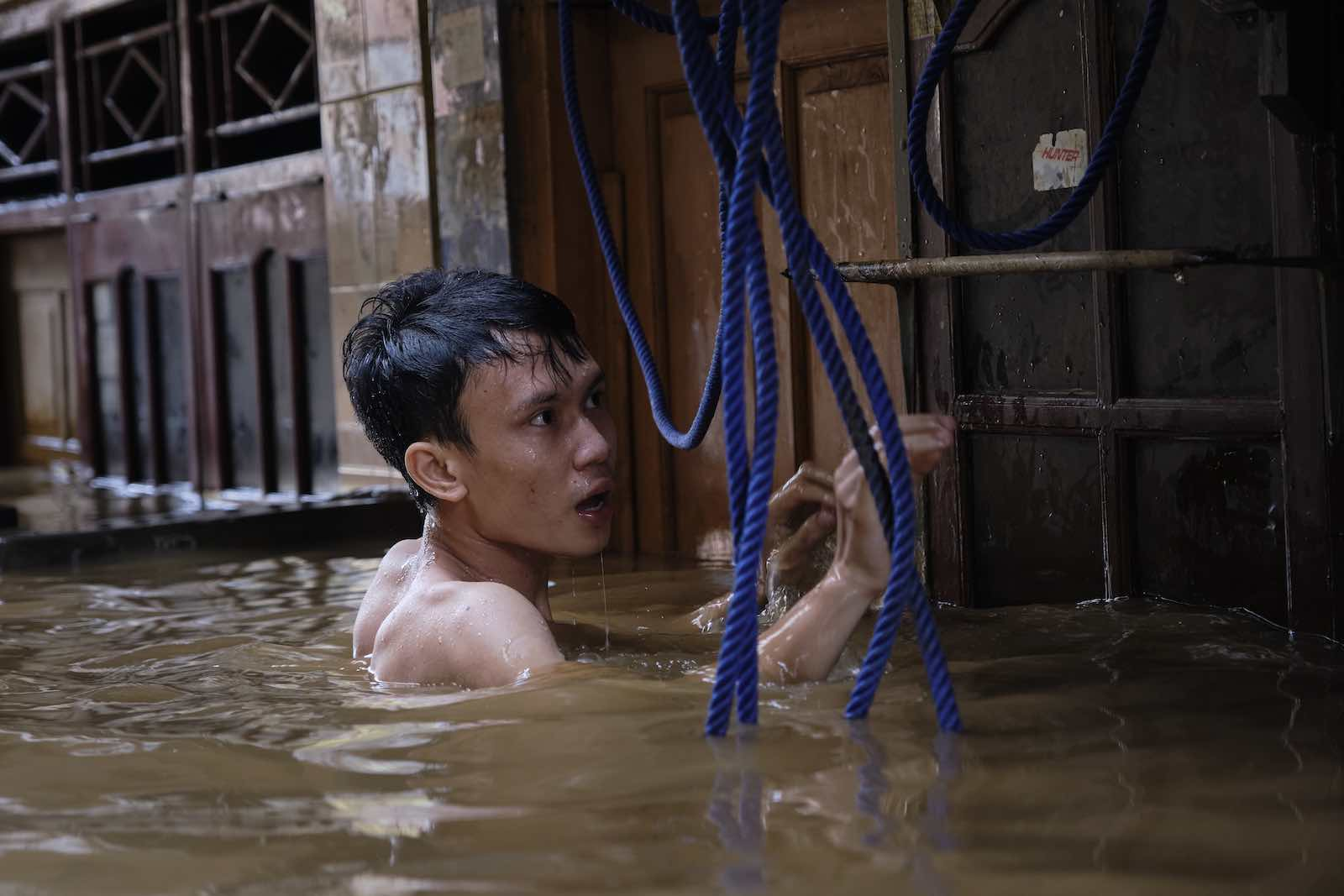 A man tries to access his house in a flooded neighbourhood in Jakarta, 2 January (Photo: Ed Wray/Getty Images)