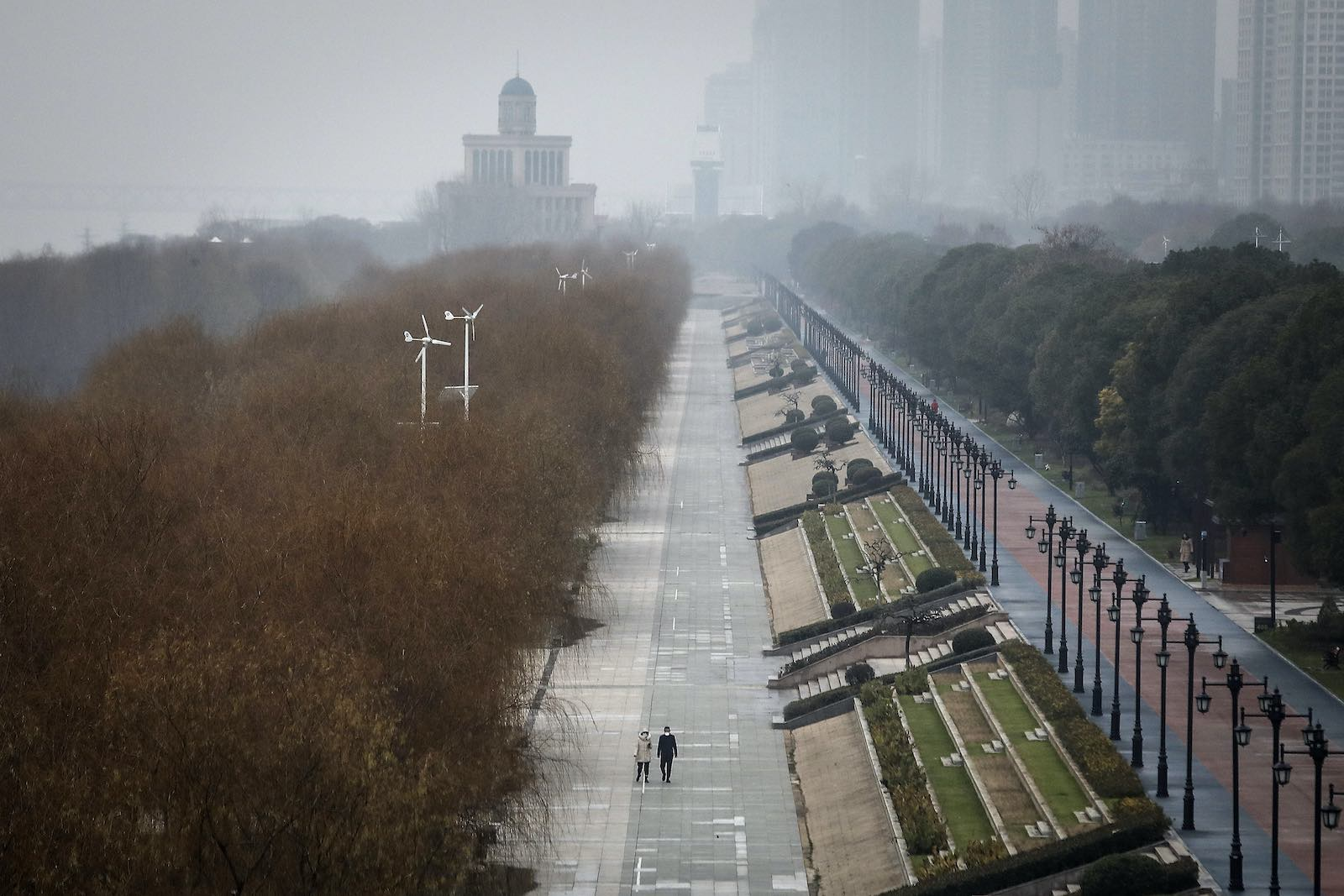 Two residents walk in an empty park in Wuhan, China, 27 January 2020 (Getty Images)