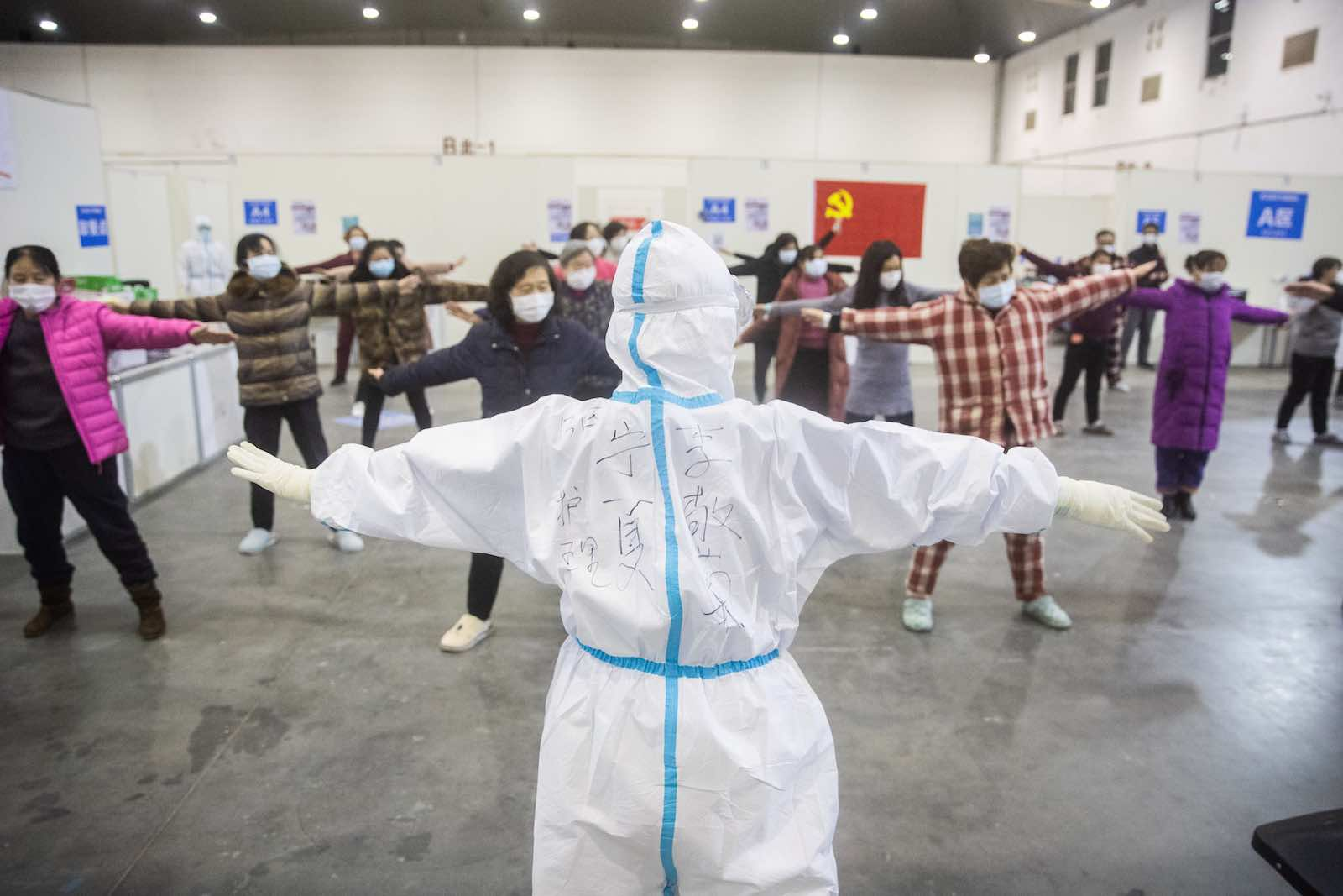 Medical staff lead patients with mild symptoms of the COVID-19 coronavirus in group exercises at an exhibition centre converted into a hospital in Wuhan, Hubei province (STR via Getty Images)