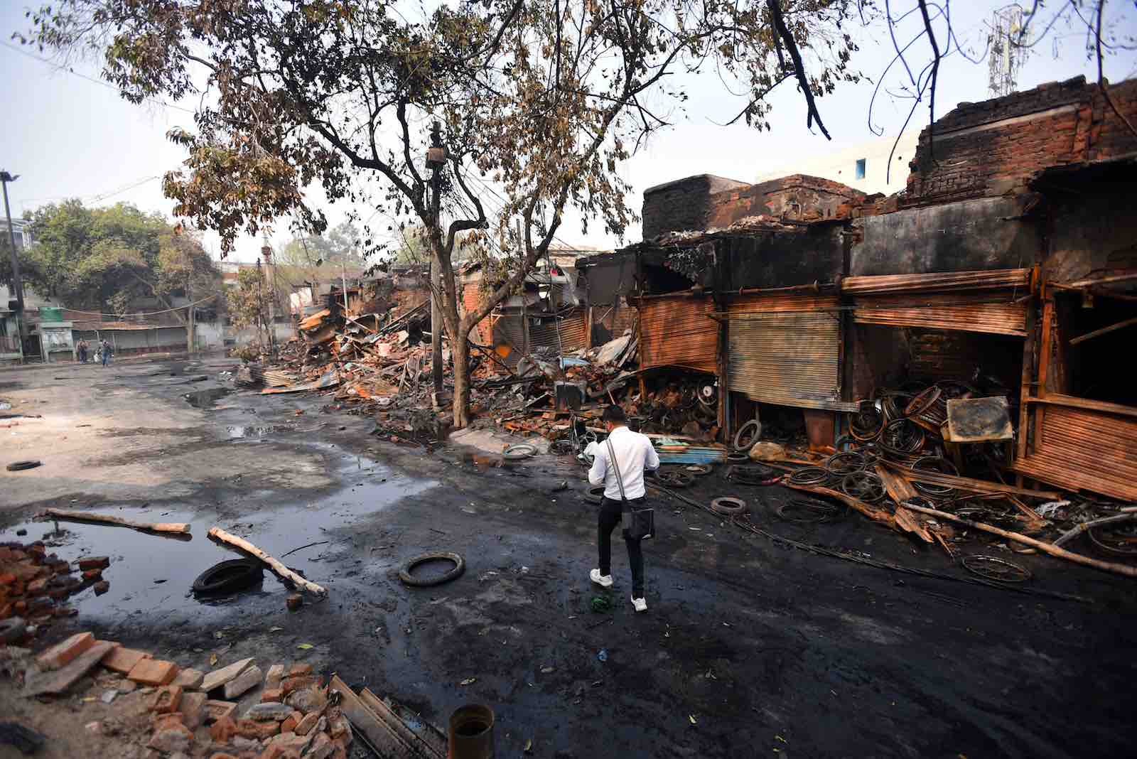A man walks past shops burnt during sectarian riots in New Delhi, 26 February (Amal KS/Hindustan Times via Getty Images)