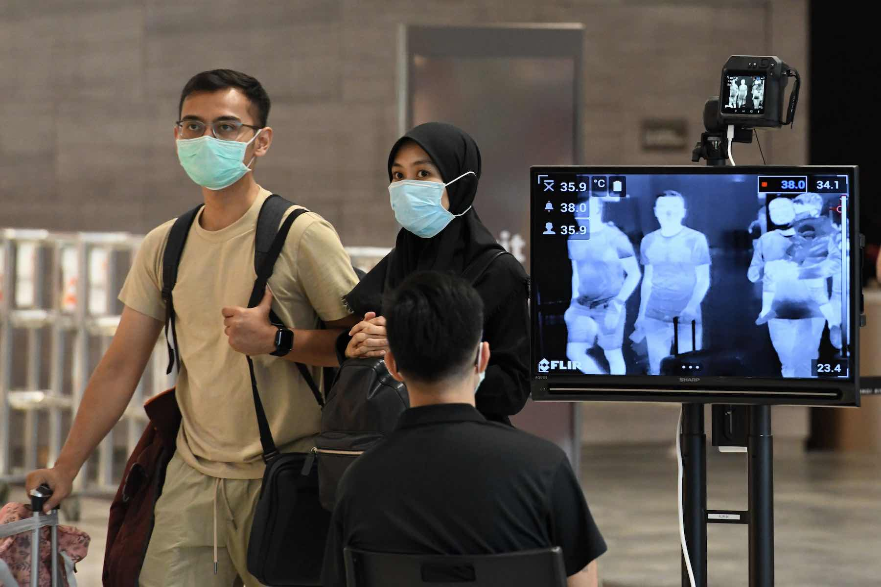 A couple walking past a temperature screening check at Changi International Airport in Singapore, 27 February 2020 (Roslan Rahman/AFP via Getty Images)