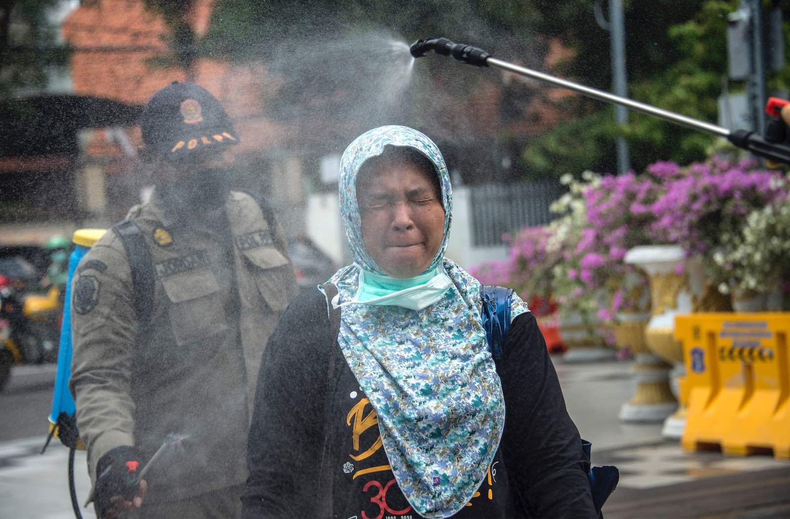 A woman is sprayed with disinfectant on Monday before entering a local government office as a precautionary move against the spread of the Covid-19 coronavirus in Surabaya, Indonesia (Juni Kriswanto/AFP/Getty Images)