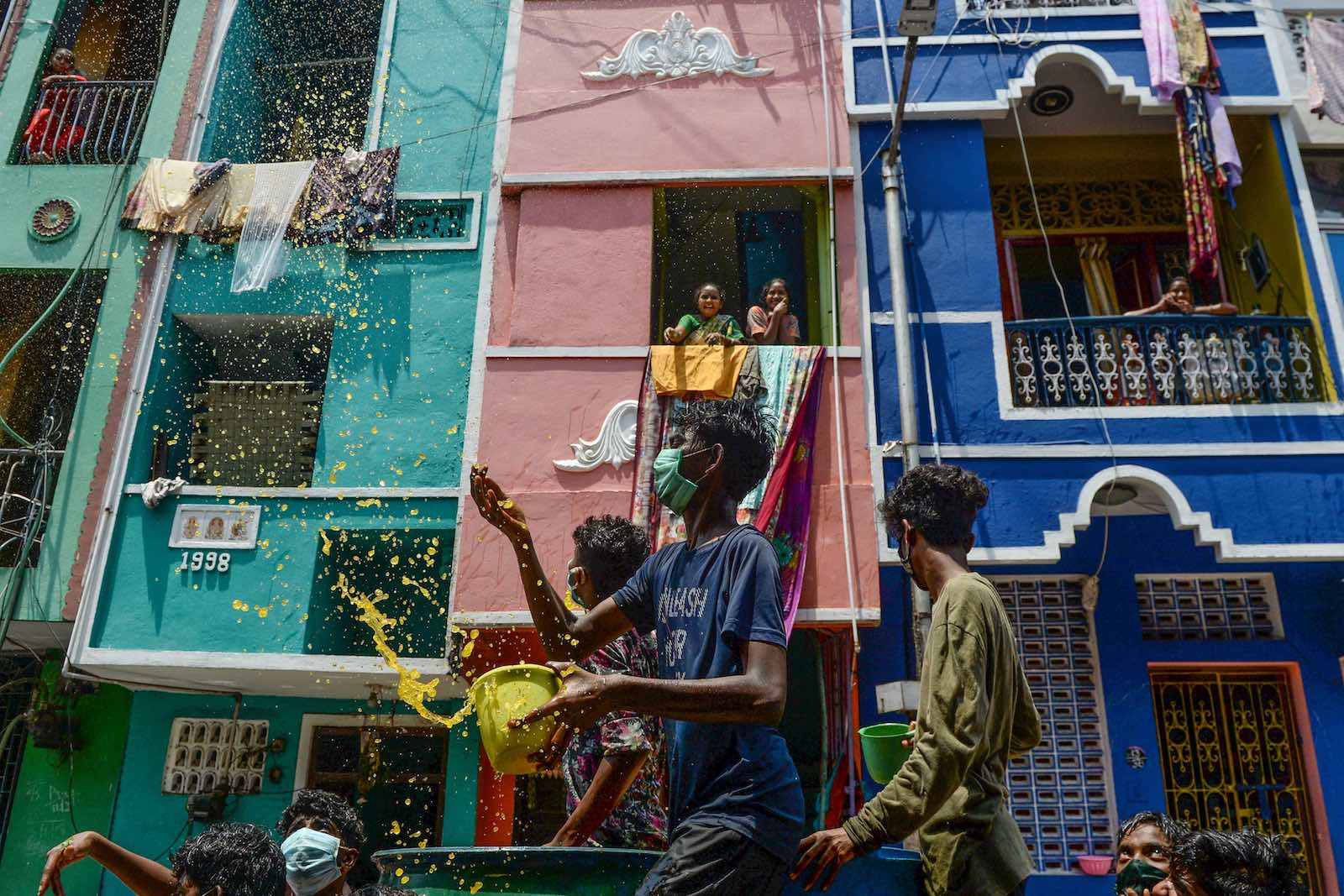 Children throw a mixture of water, neem herb, and turmeric in what is said to be a natural disinfectant on a Chennai street during a government-imposed nationwide lockdown (Arun Sankar/AFP/Getty Images)
