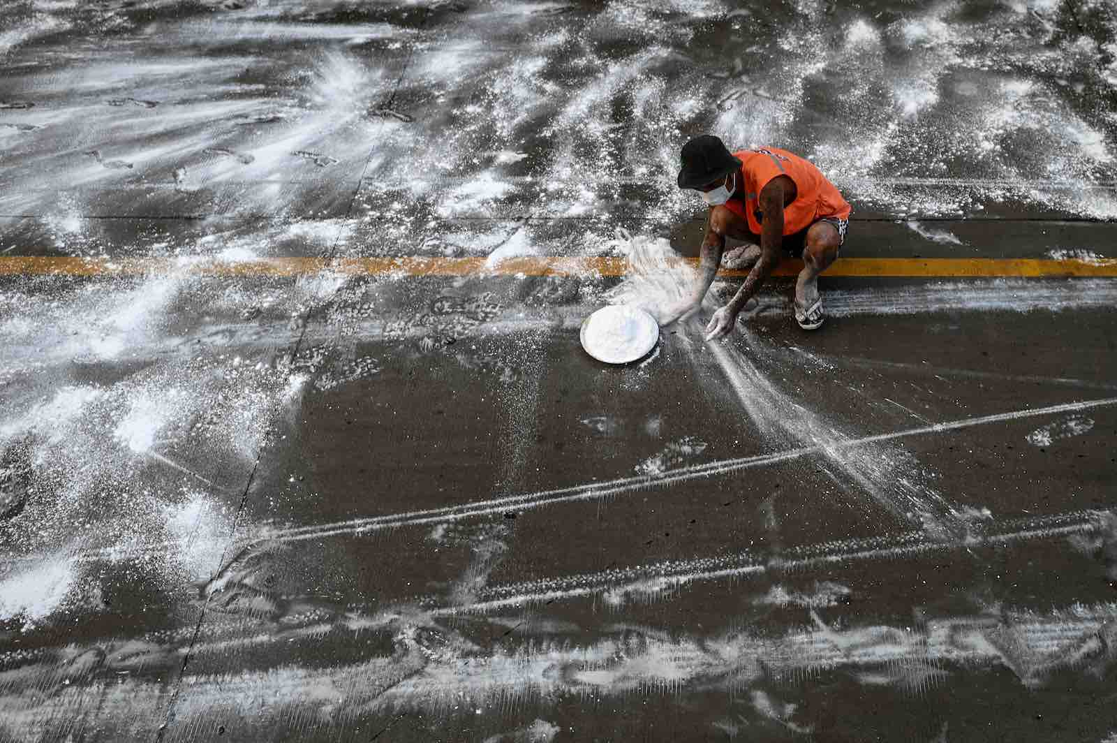 A volunteer spreads lime on a road as a preventive measure against Covid-19, Yangon, 22 April (Ye Aung Thu/AFP via Getty)