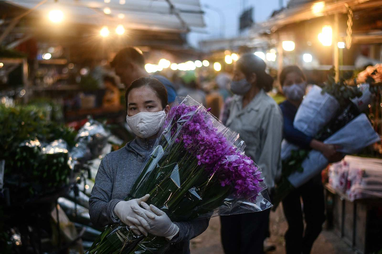 A woman carries flowers at the Quang Ba flower market in Hanoi, 11 May (Manan Vatsyayana/AFP via Getty Images)
