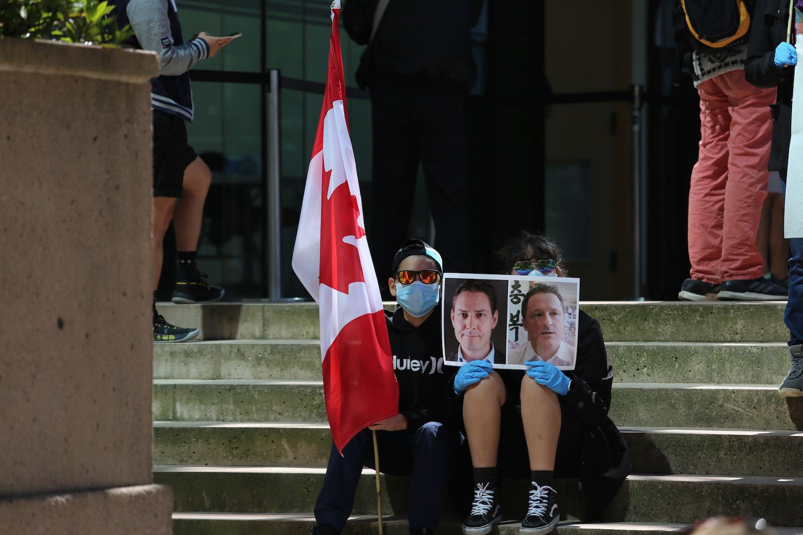 Protesters outside a court hearing for Meng Wanzou hold pictures of Michael Kovrig and Michael Spavor, Vancouver, Canada, 27 May 2020 (Mert Alper Dervis/Anadolu Agency via Getty Images)