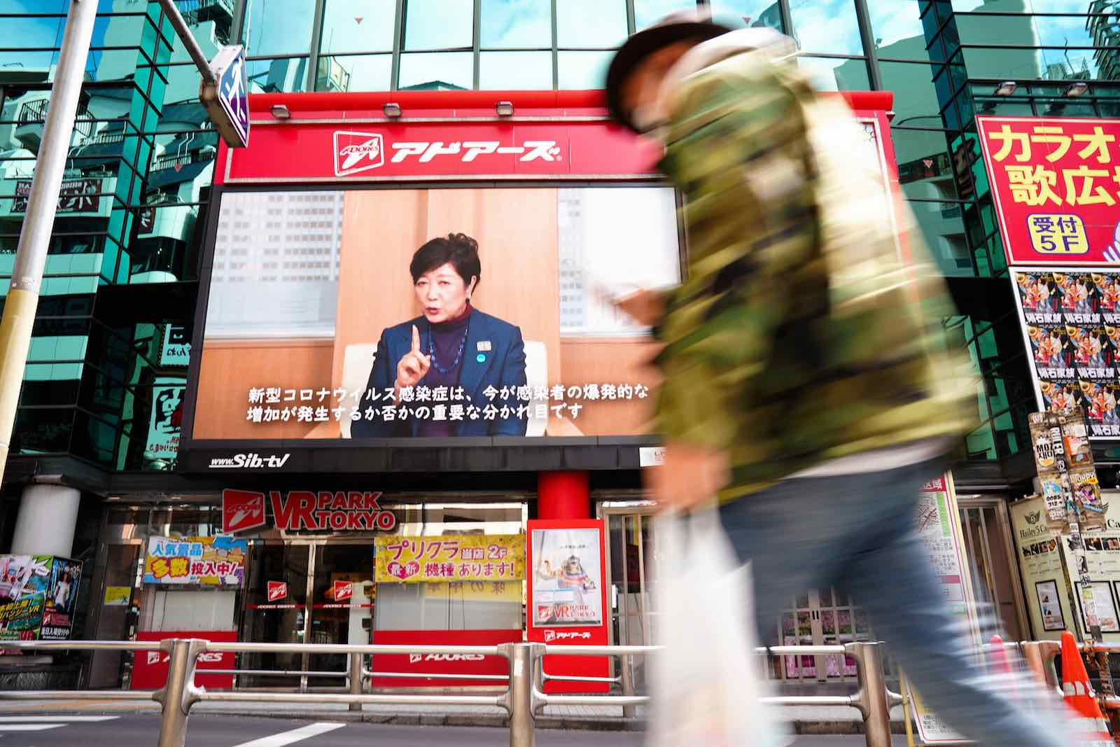 Governor Yuriko Koike on a video screen in Tokyo's Shibuya district requesting residents to follow Covid-19 stay-at-home orders, 11 April 2020 (Asahi Shimbun via Getty Images)