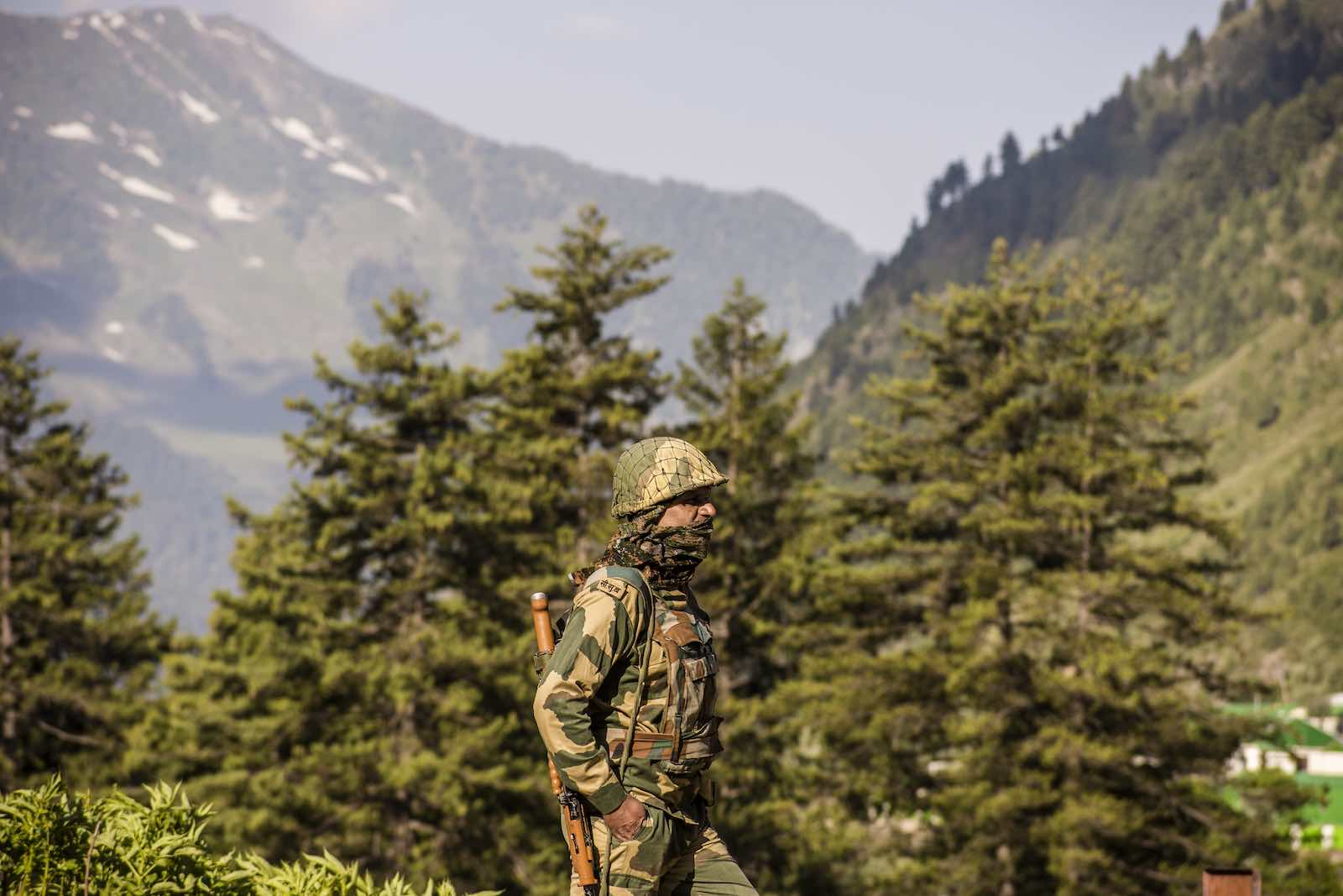 An Indian Border Security Force soldier guards a highway as Indian army convoy travels towards Leh, bordering China, on 19 June in Gagangir, India (Yawar Nazir/Getty Images)