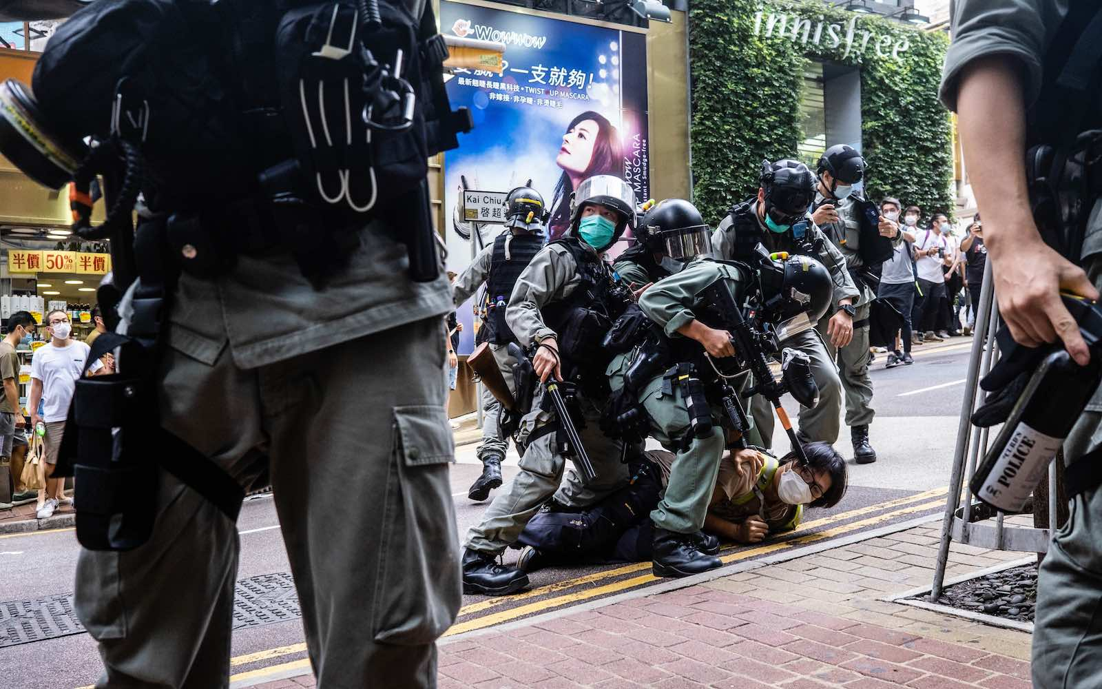 Riot police pin down a protester during a demonstration after the passage of a new security law in Hong Kong, 1 July 2020 (Willie Siau/SOPA Images/LightRocket via Getty Images)