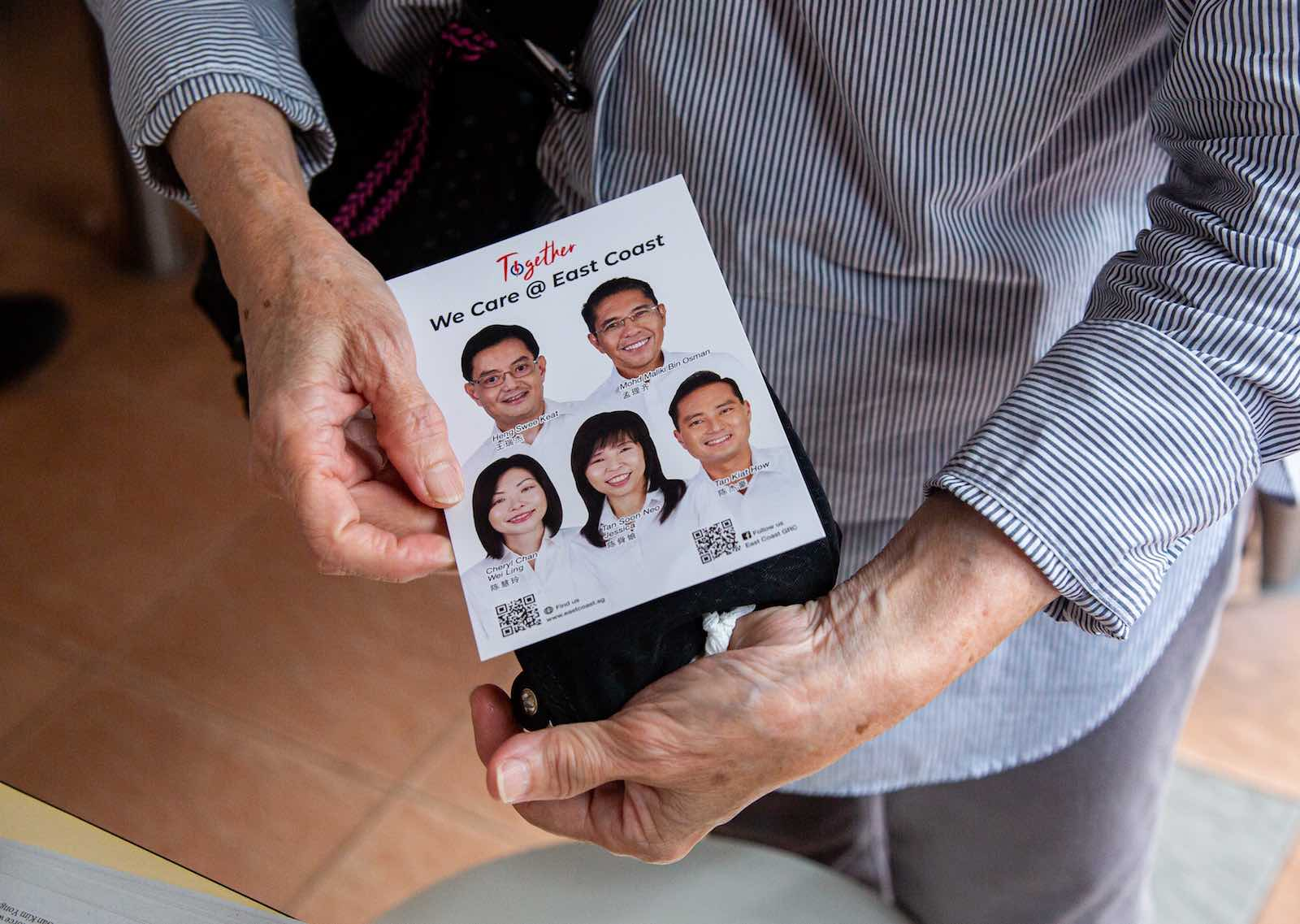 A resident holds a PAP campaign leaflet of East Coast Group Representation Constituency, 3 July 2020 (Ore Huiying/Getty Images)