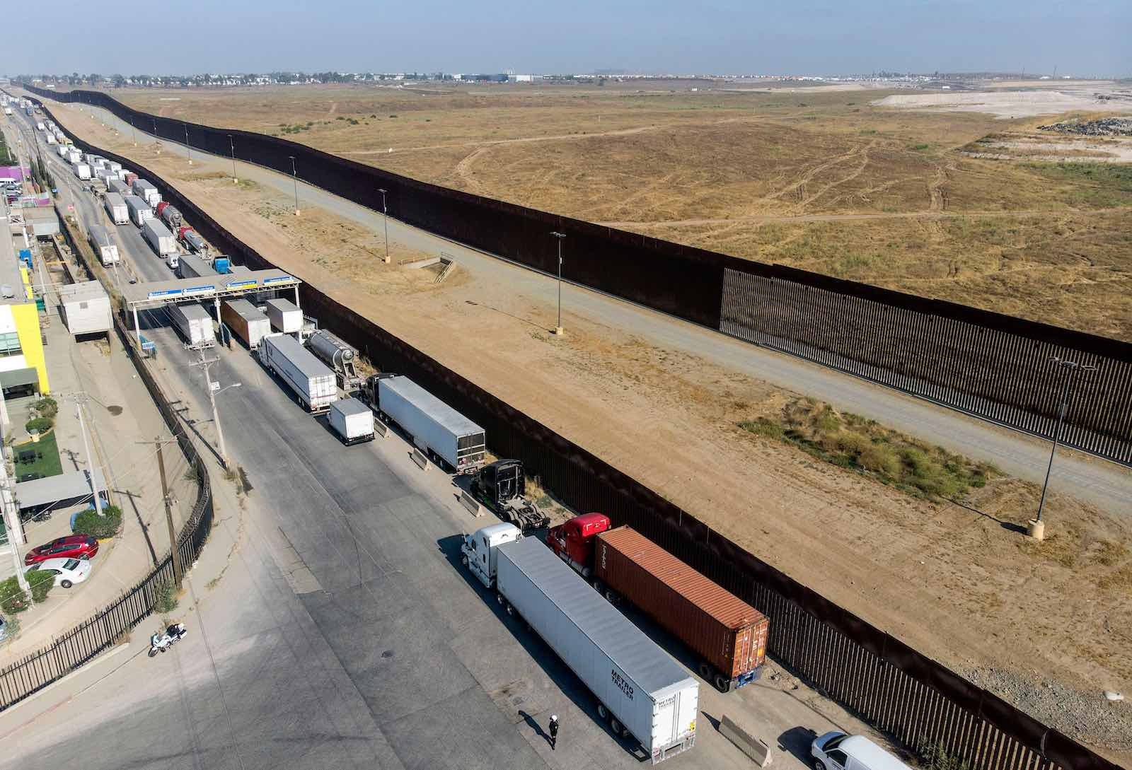 Trucks queue to cross the border into the US at the Otay commercial crossing point in Tijuana, Mexico, 7 July 2020 (Guillermo Arias/AFP via Getty Images)