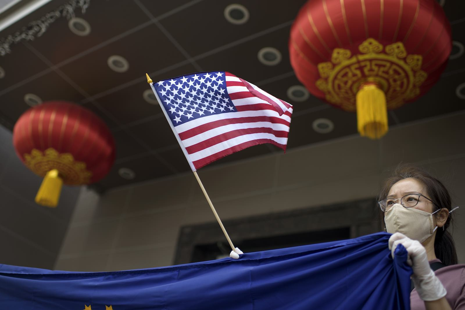 A protester holds a US flag outside of the Chinese consulate in Houston after the Trump administration ordered it be closed (Mark Felix/AFP via Getty Images)