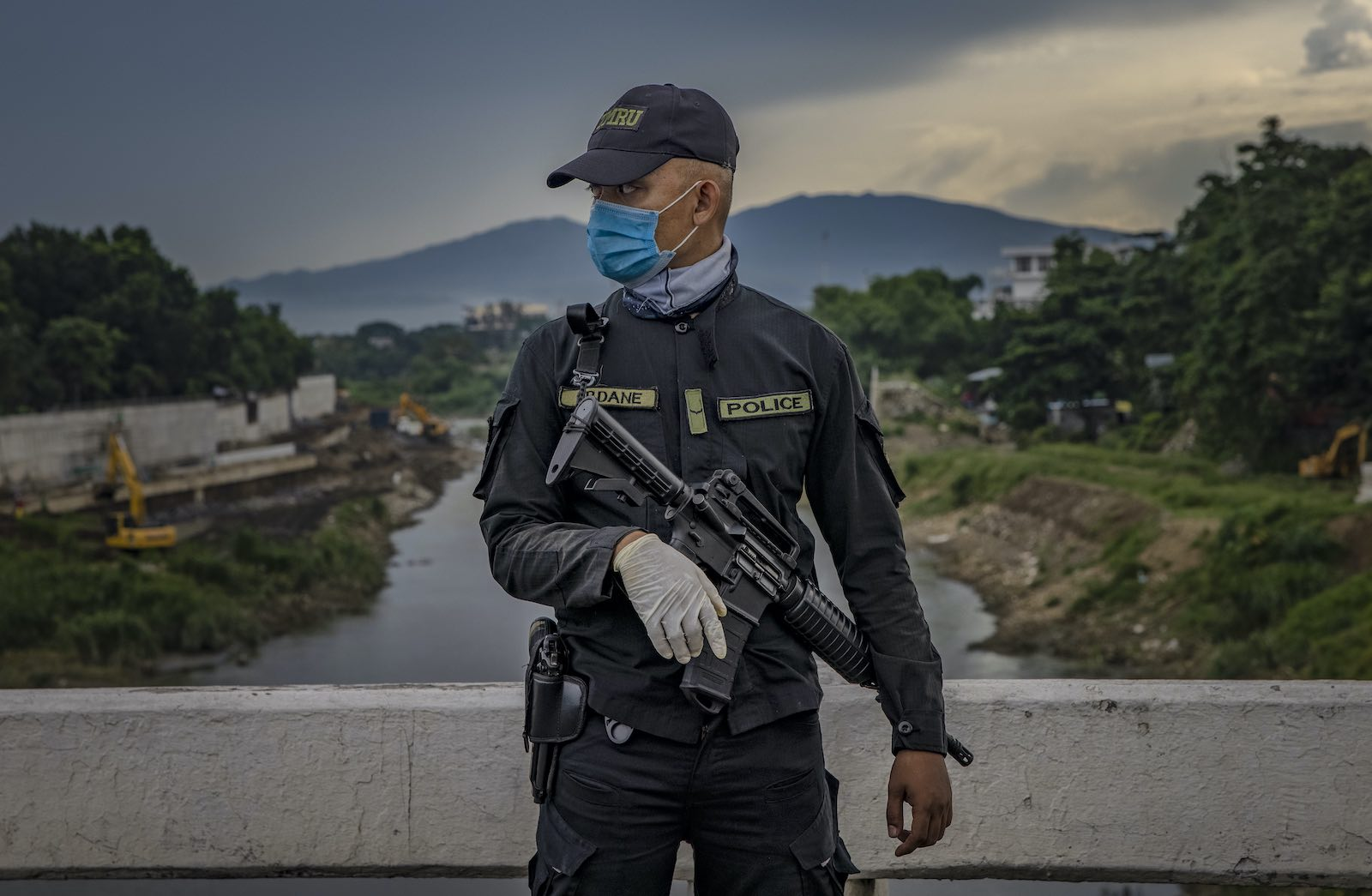 A police officer stands guard at a quarantine checkpoint in Quezon city, Philippines, 4 August 2020 (Ezra Acayan/Getty Images)