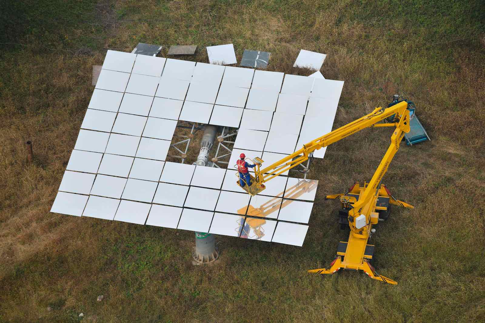 A worker replacing mirrors on a heliostat at the Yanqing Solar Thermal Power Generation Base, in Yanqing, China, north of Beijing, 28 September 2020 (Greg Baker/AFP via Getty Images)