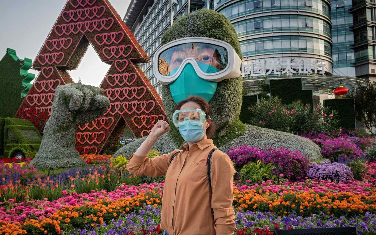 A woman poses in front of a flower display dedicated to frontline healthcare workers during the Covid-19 pandemic, Beijing, 29 September 2020 (Nicolas Asfouri/AFP via Getty Images)