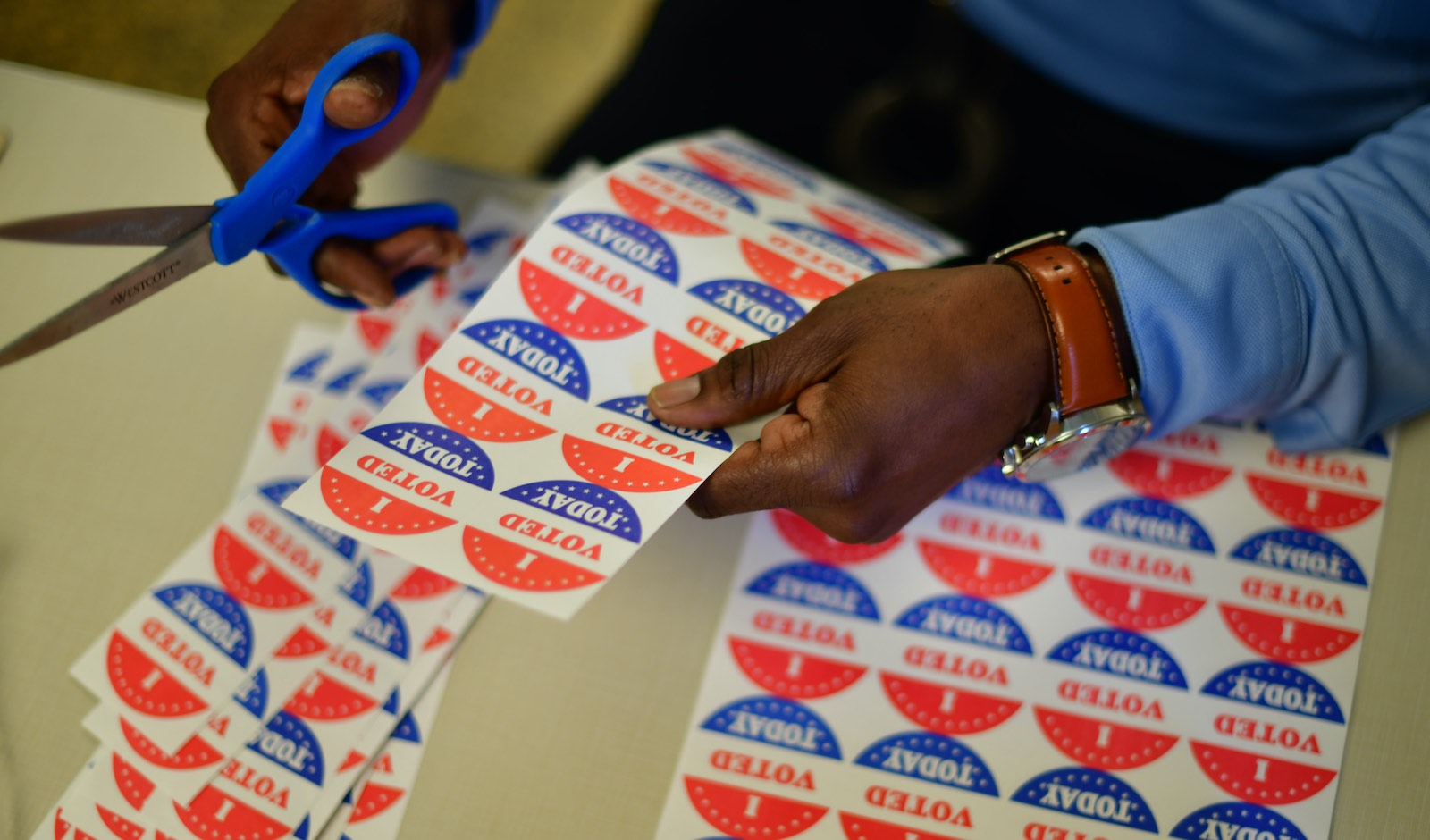 A volunteer cuts out stickers for voters at a polling station in Philadelphia, Pennsylvania, a key state in this year's election (Mark Makela/Getty Images)