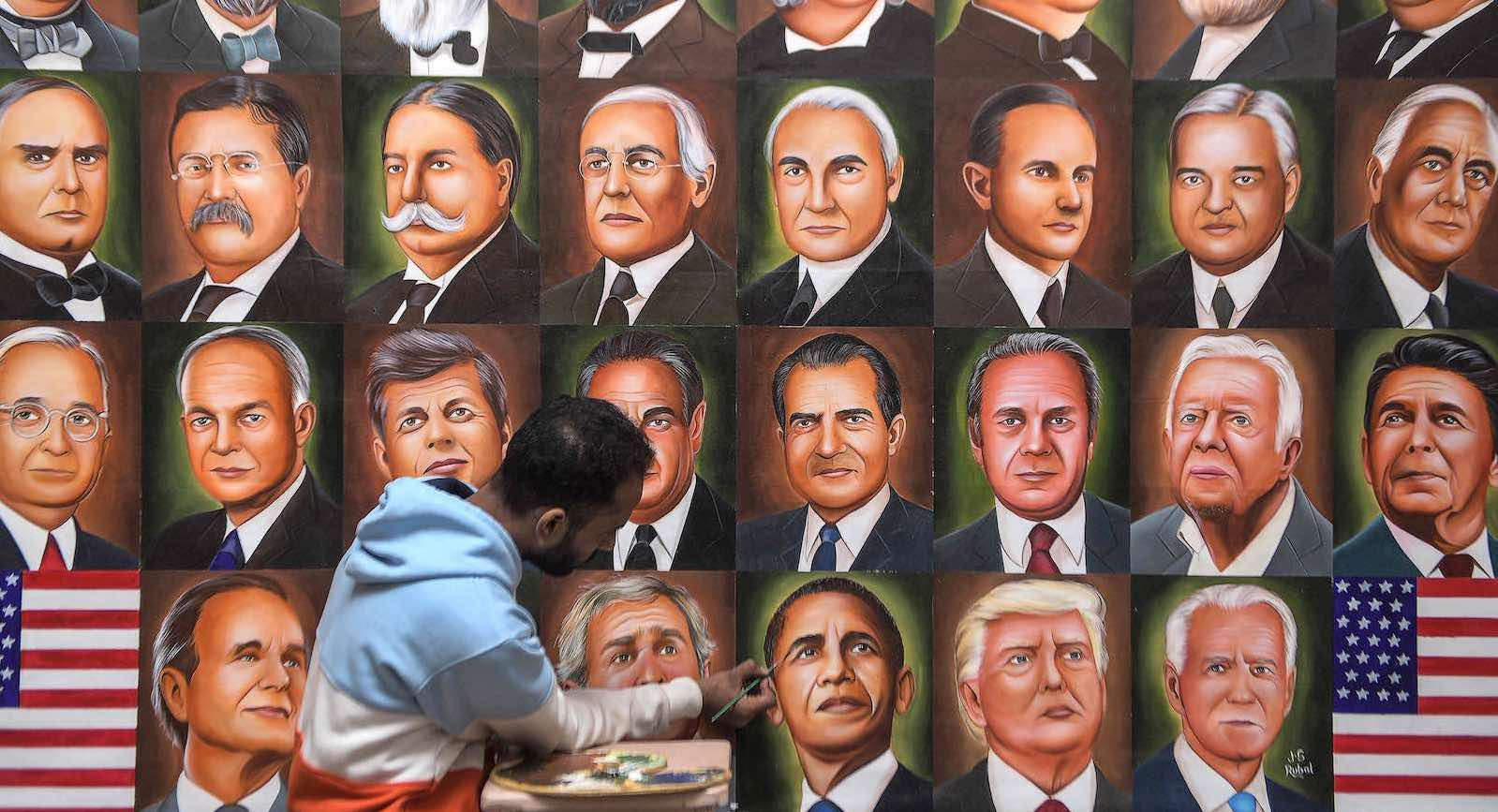 A painter puts the finishing touches on a mural of US presidents in Amritsar, India, 8 November 2020 (Narinder Nanu/AFP via Getty Images)