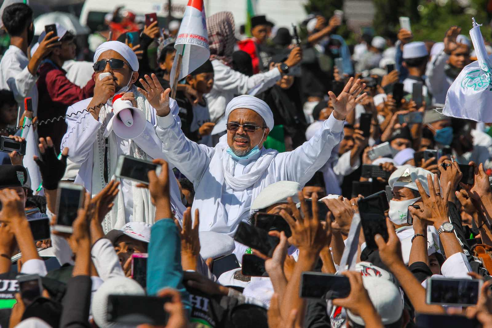 Muslim cleric Rizieq Shihab gestures to supporters as he arrives to inaugurate a mosque in Bogor, Indonesia, 13 November (Rangga Firmansyah/NurPhoto via Getty Images)