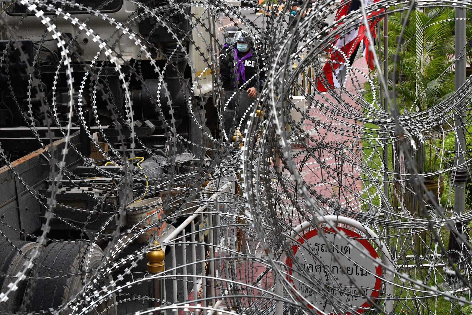Police stand behind coils of barbed wire ahead of expected pro-democracy protests in Bangkok on 18 November (Mladen Antonov/AFP via Getty Images)